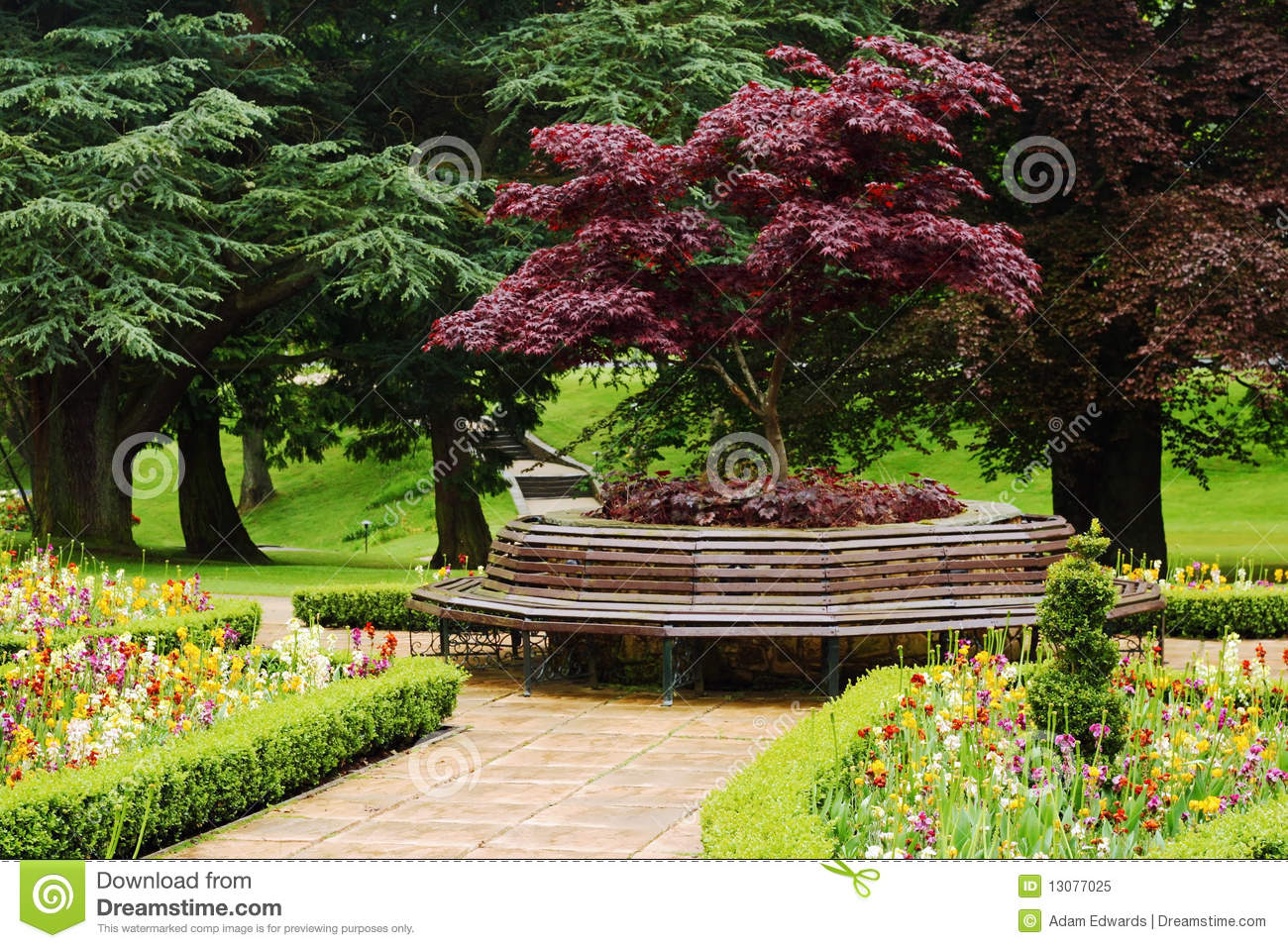 Vibrant Floral Garden With Round Bench Royalty Free Stock
