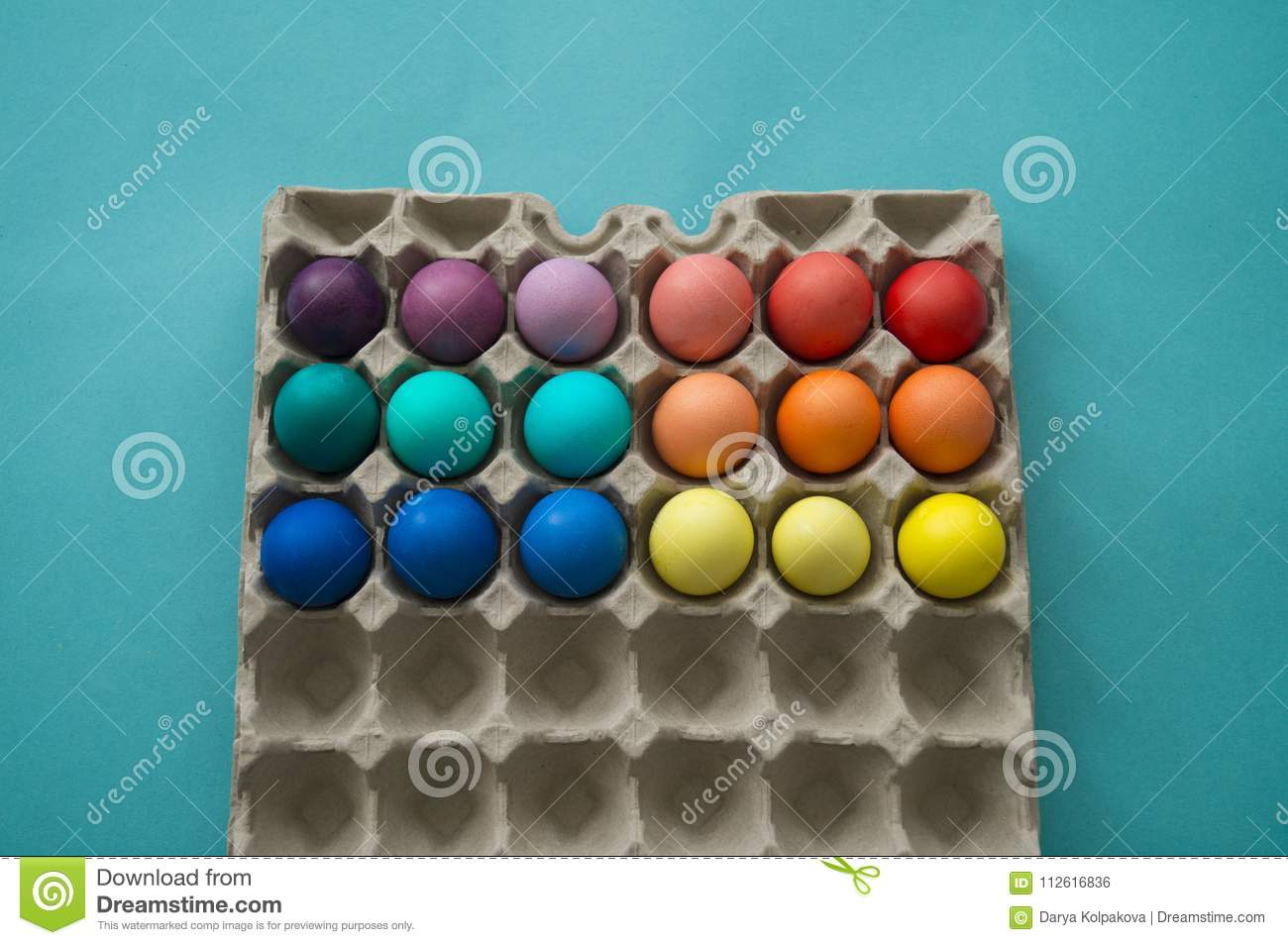 Vibrant hand dyed colorful Easter eggs in a cardboard egg box viewed