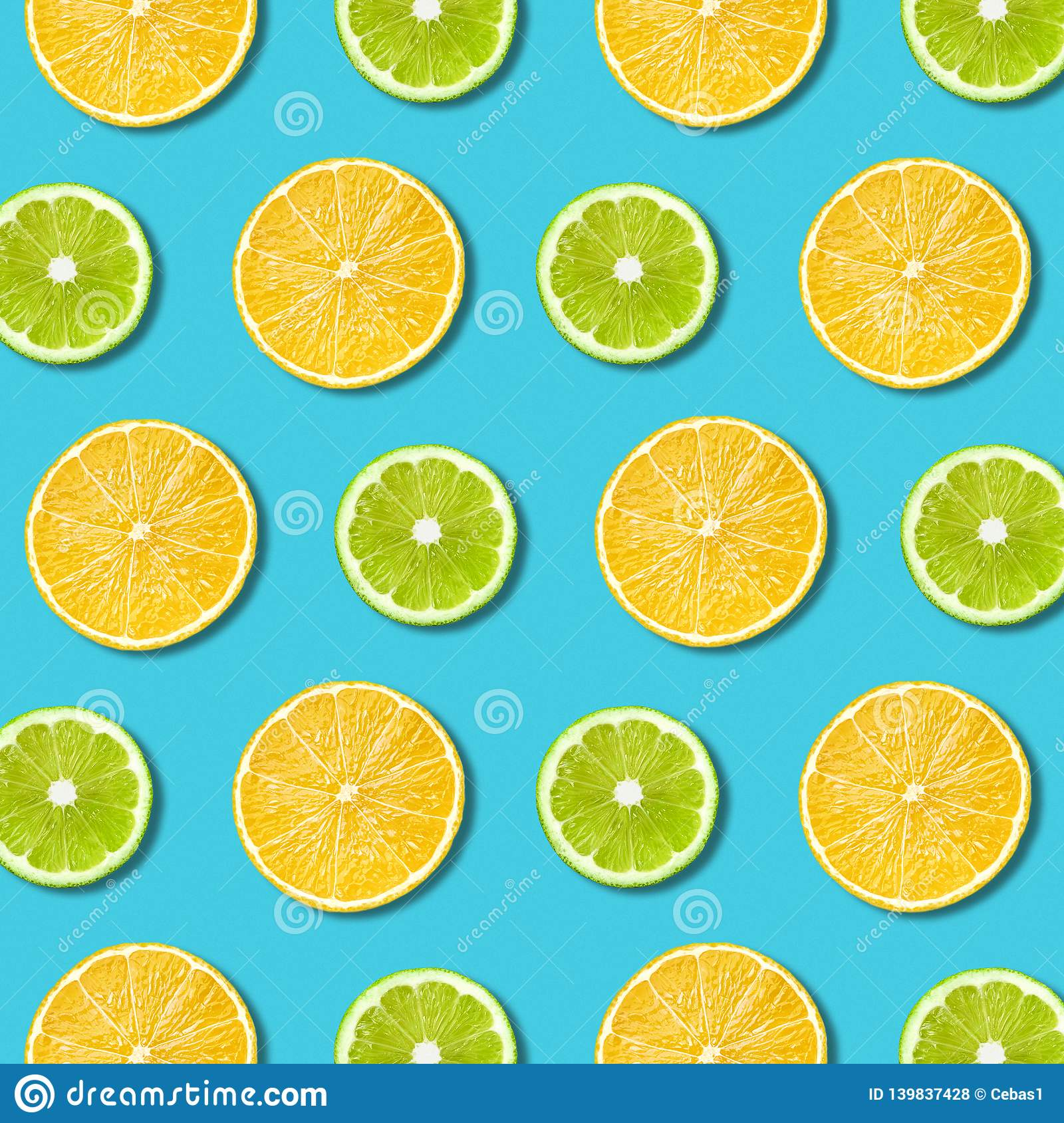 Vibrant lemon and green lime slices texture on turquoise background