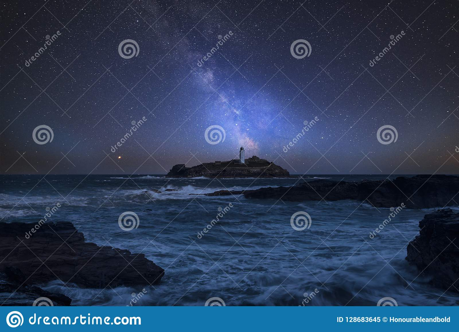 Vibrant Milky Way composite image over landscape of Godrevy Lighthouse in Corwnall England