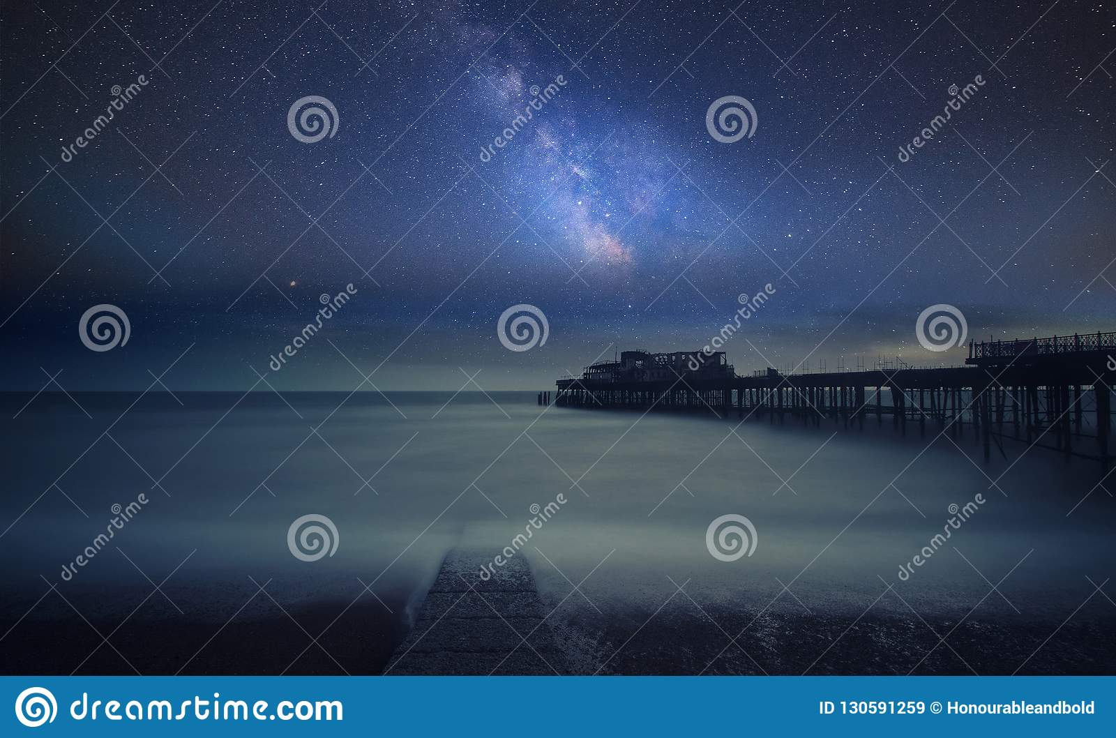 Vibrant Milky Way composite image over landscape of Long exposure of ruined pier at sea