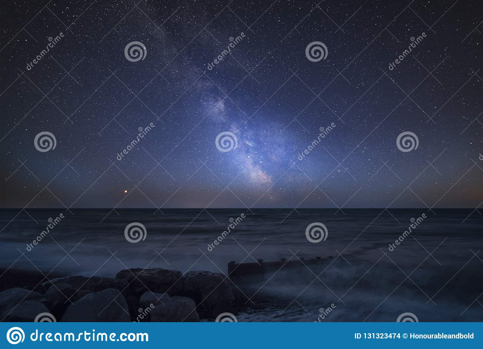 Vibrant Milky Way composite image over landscape of pier at sea