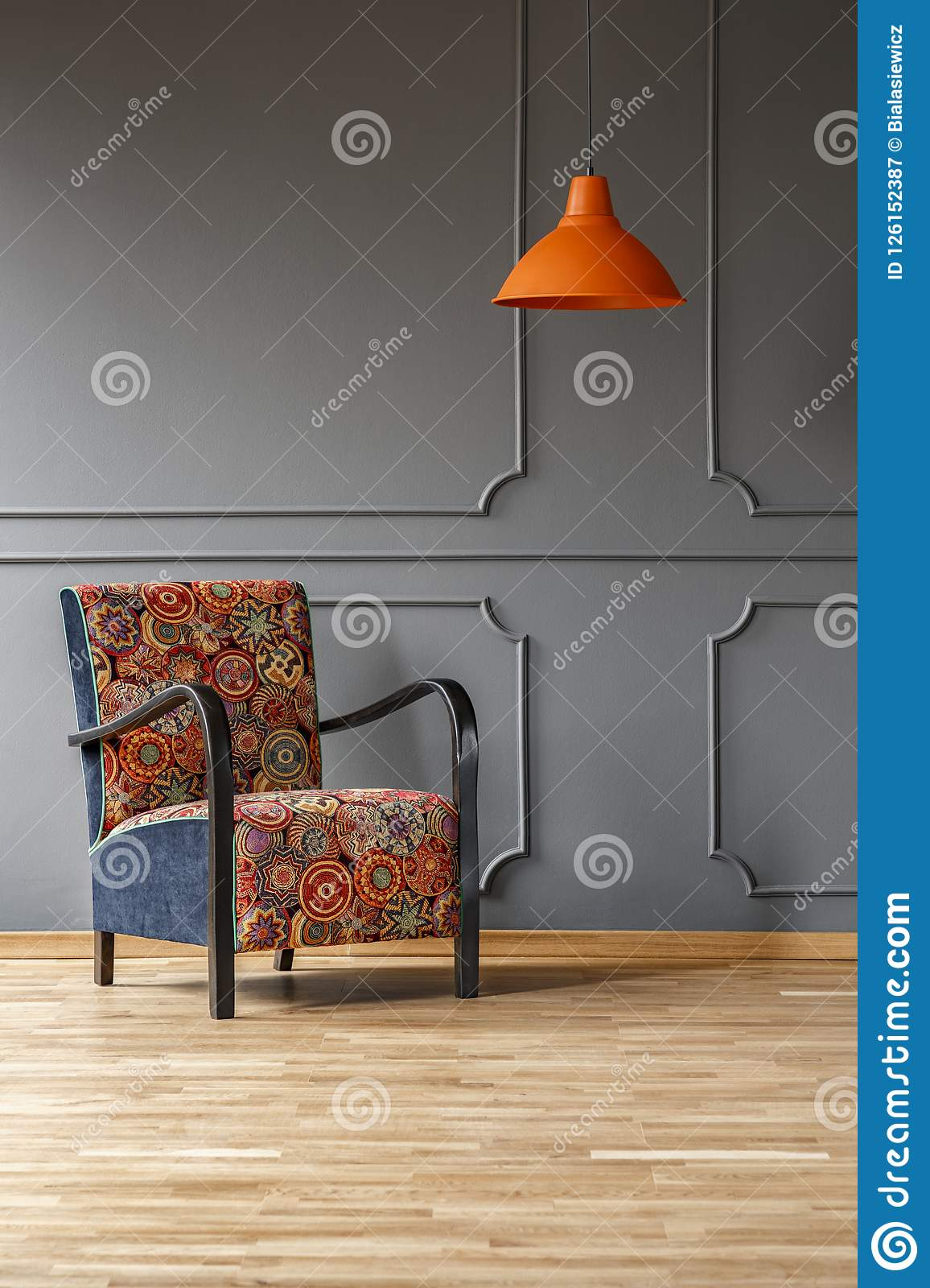 Vibrant orange ceiling light and a comfortable armchair with a colorful boho pattern in a gray living room interior with place for