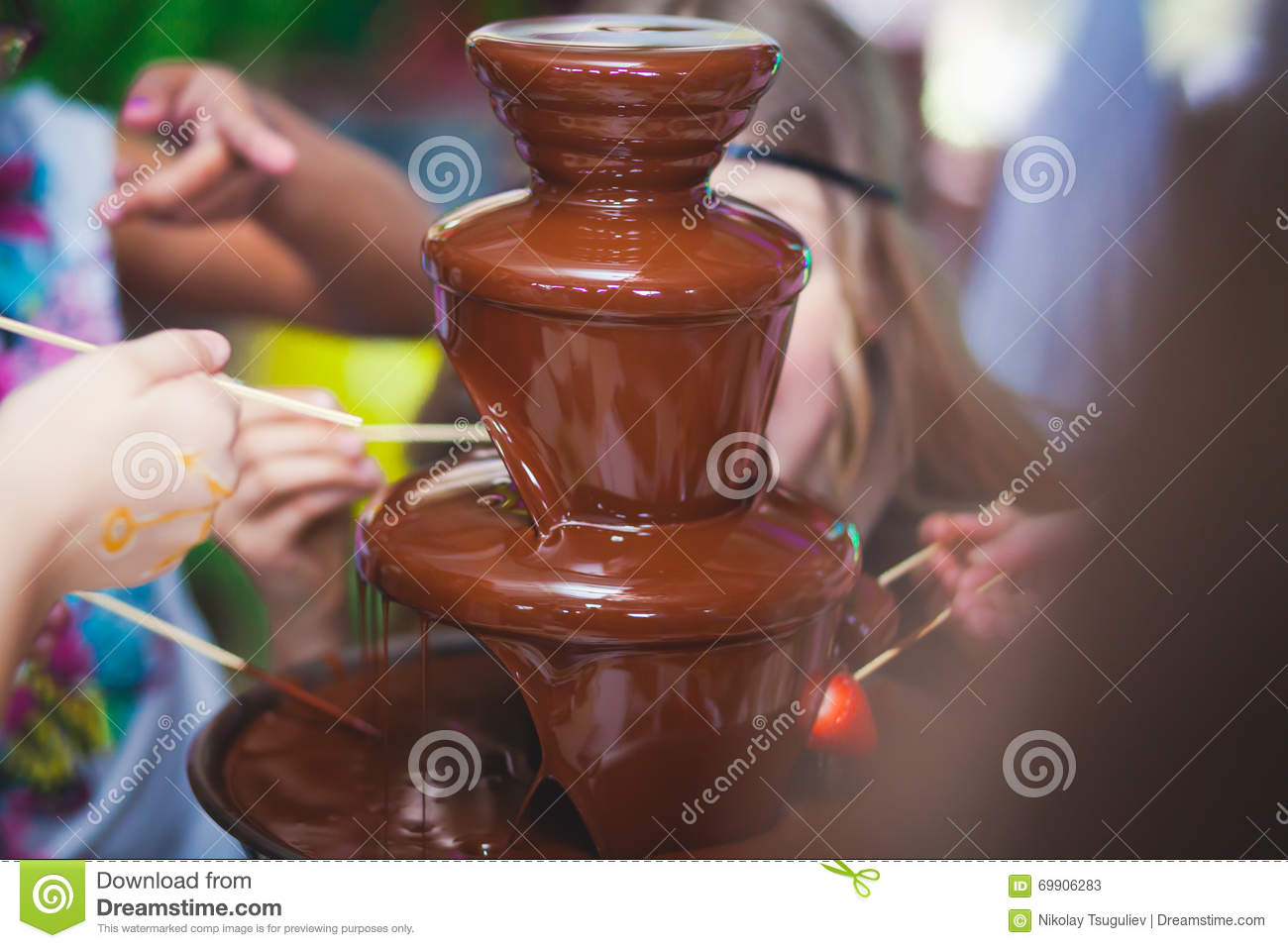 Vibrant Picture of Chocolate Fountain Fontain on childen kids birthday party with a kids playing around and marshmallows and fruit