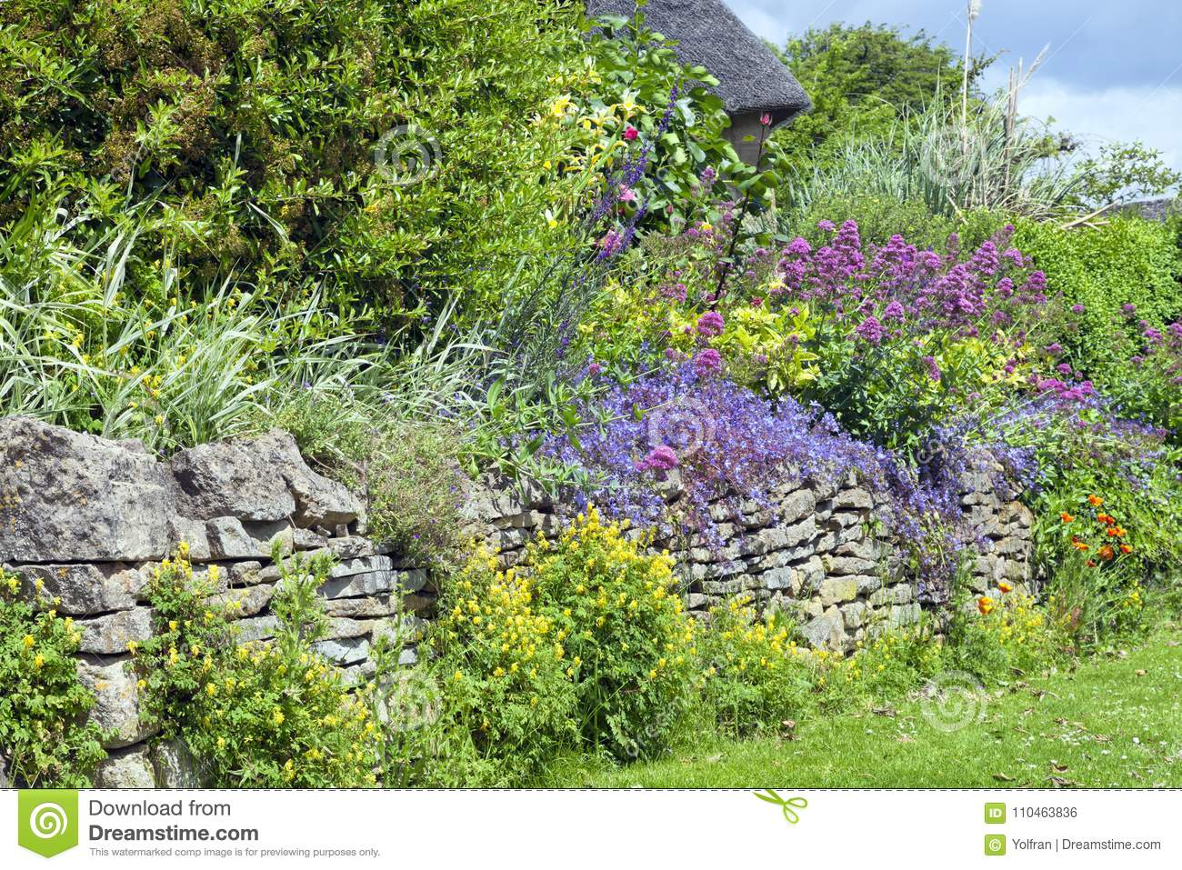 Cottage Garden Colorful Floral Display On Stone Wall Stock Photo