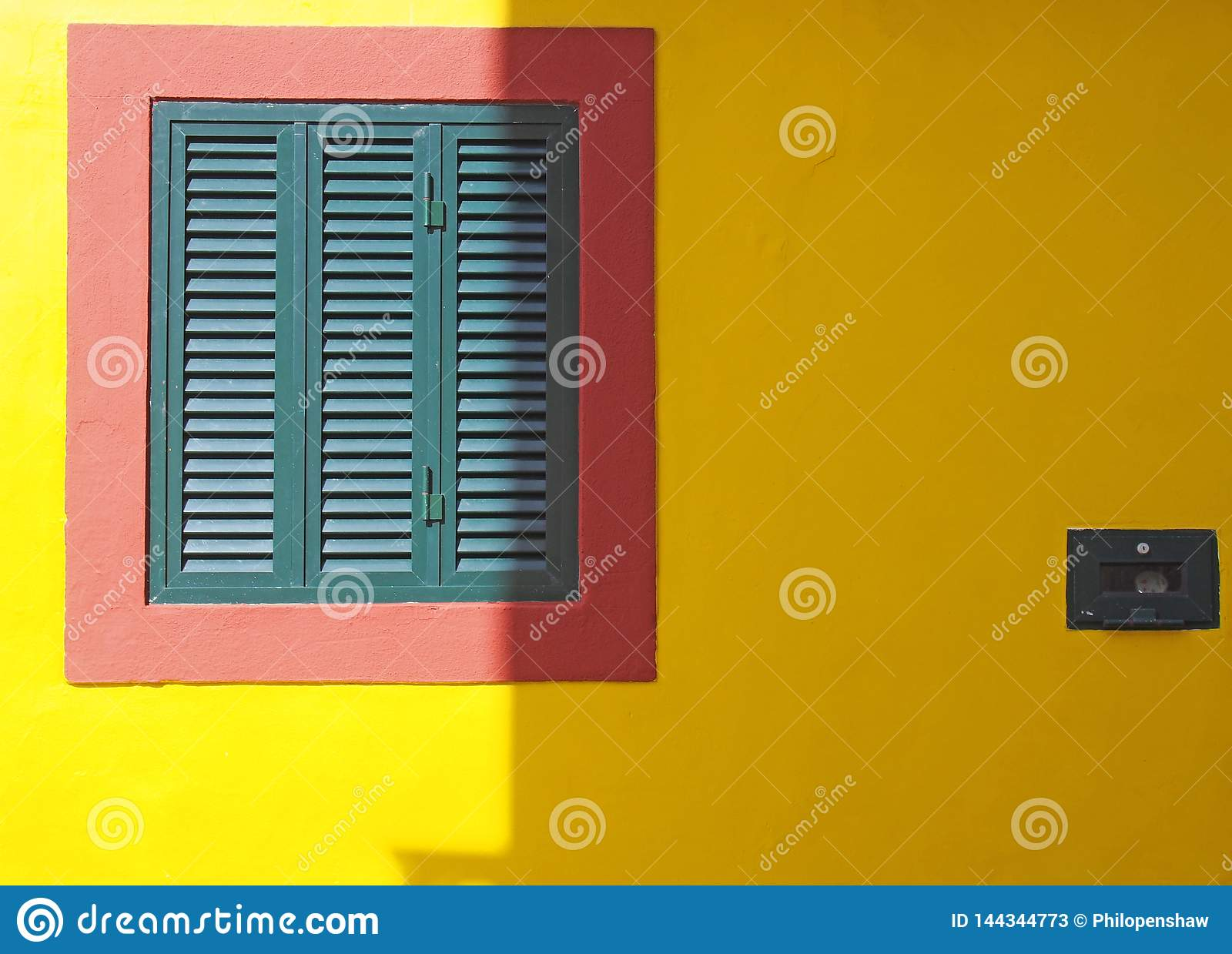 a vibrant yellow wall with red frame and green closed shuttered window typical Portuguese colors in bright sunlight and shade with