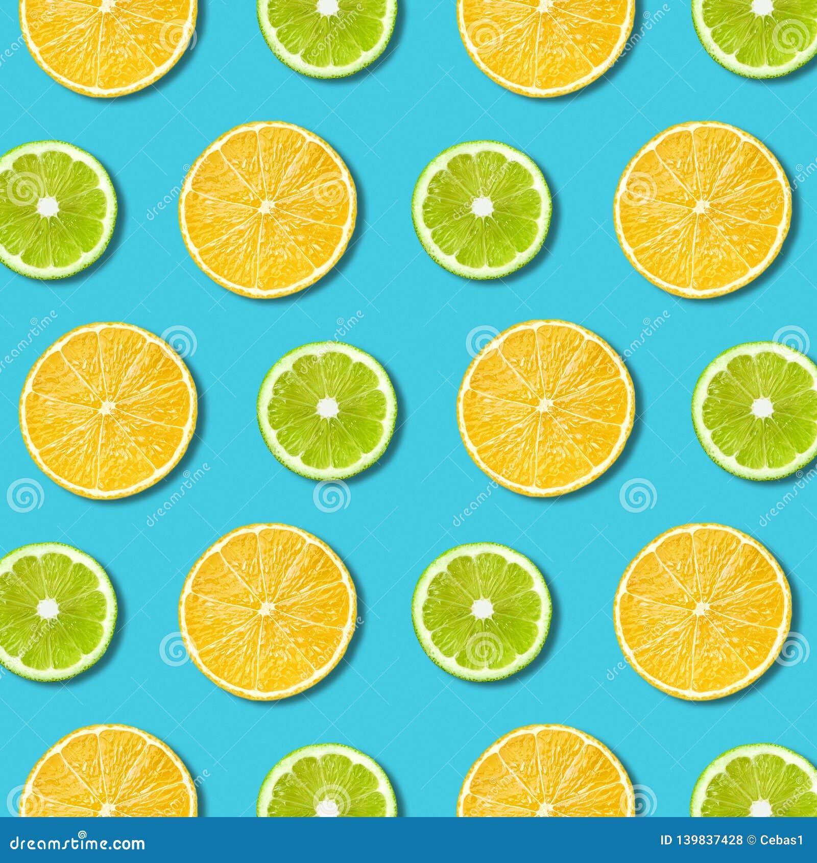Vibrerande citron och grön limefruktskivatextur på turkosbakgrund