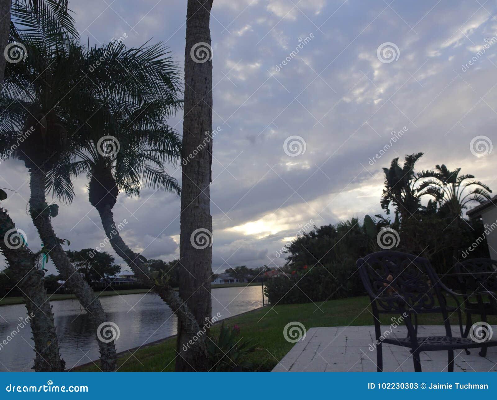 Vibrierender und stürmischer Sonnenuntergang in den Tropen mit einem Schattenbild von a