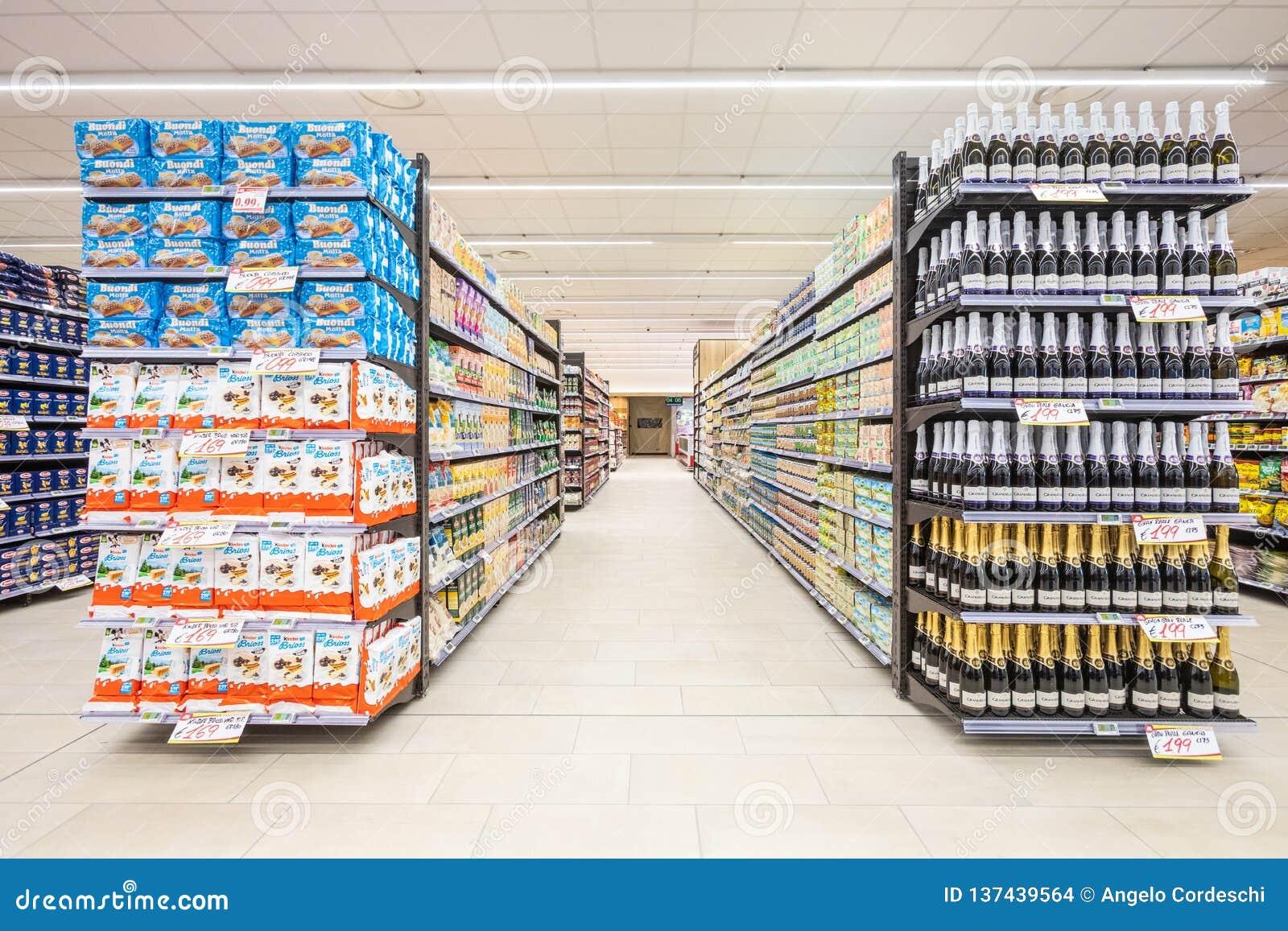Vicoli degli scaffali con la navata laterale dei prodotti delle merci dentro un supermercato