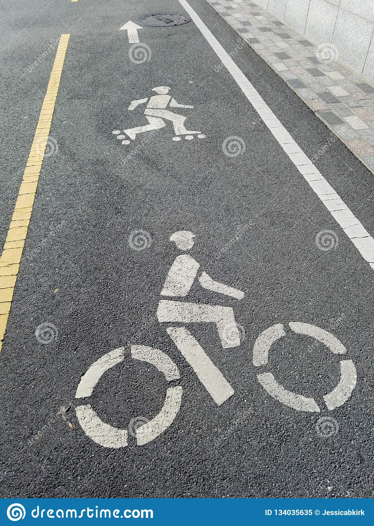 Vicolo di pattinaggio a rotelle sul percorso della bici, con gli indicatori per le linee di demarcazione gialle e bianche dei pat