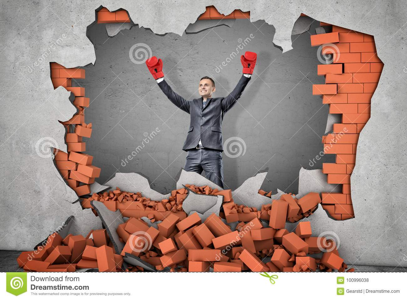 A victorious businessman in boxing gloves stands near a hole in a brick wall with rubble lying around.