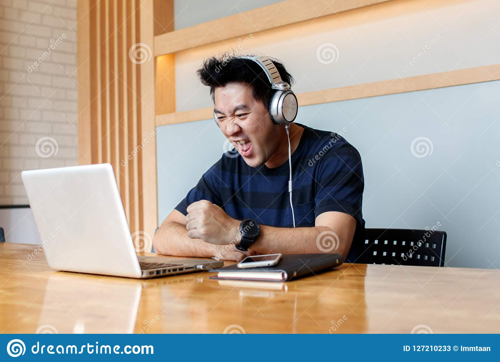 Vidéo de observation de blogger masculin dans les réseaux sociaux par l intermédiaire des écouteurs tout en mettant à jour le log