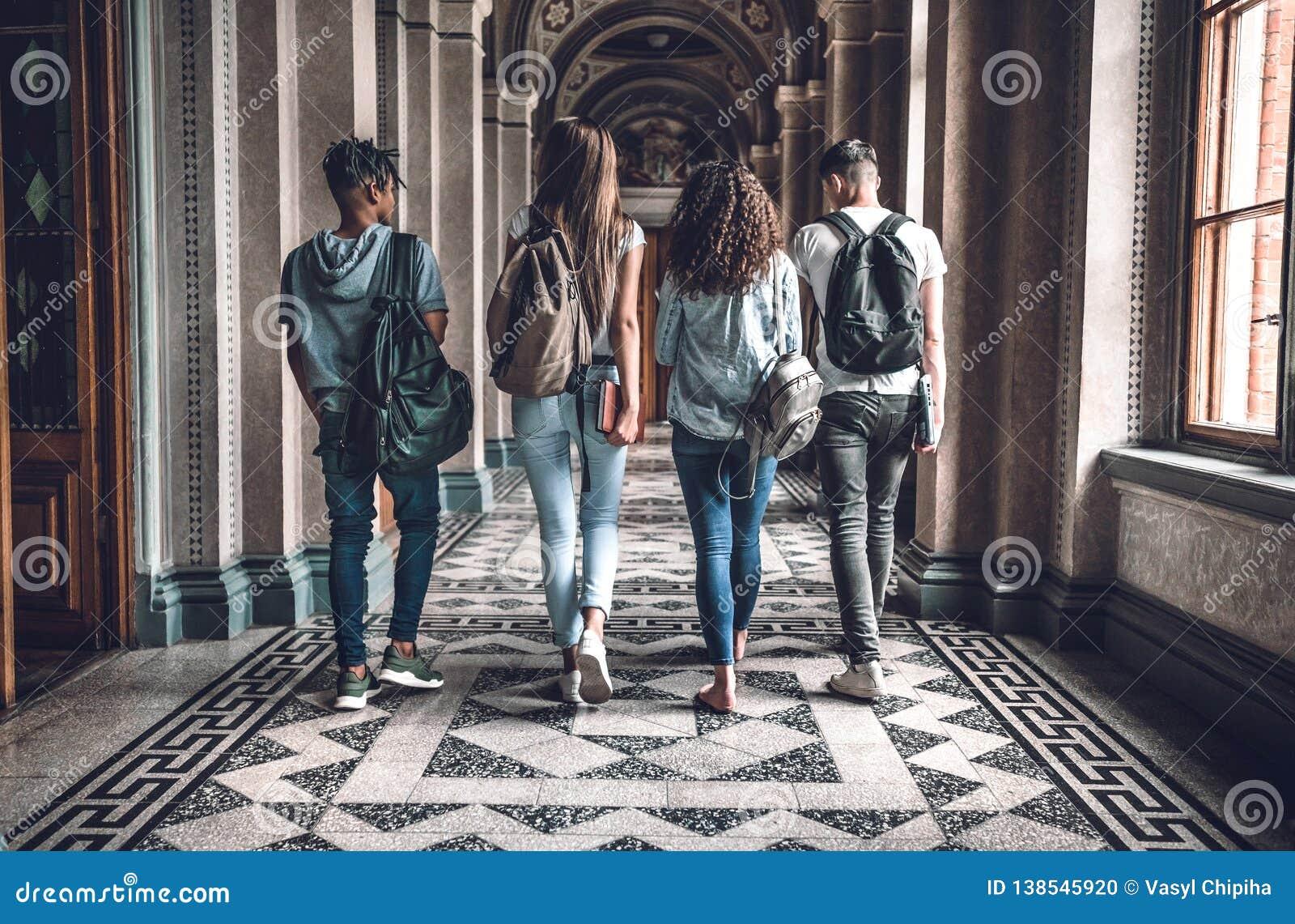 Vida de la universidad El grupo de estudiantes está caminando en pasillo y la charla de la universidad