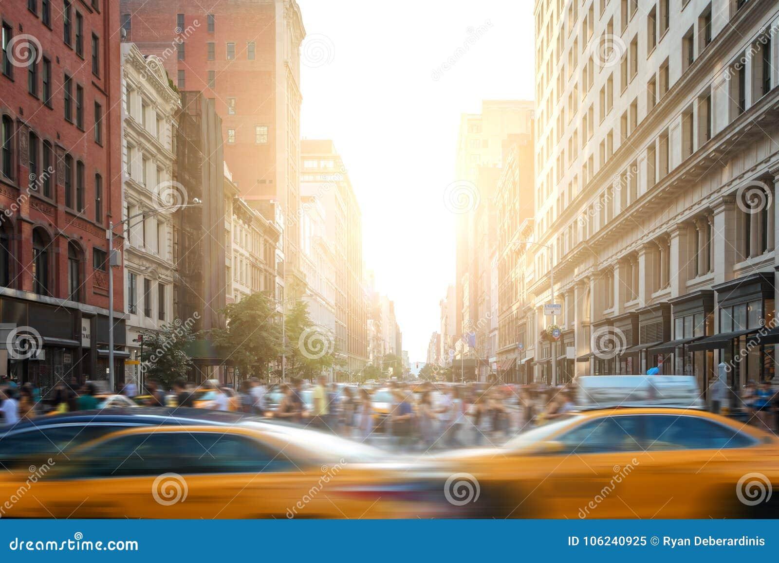 Vida rápida en escena de la calle de New York City con los taxis que conducen abajo de la 5ta avenida y muchedumbres de gente en