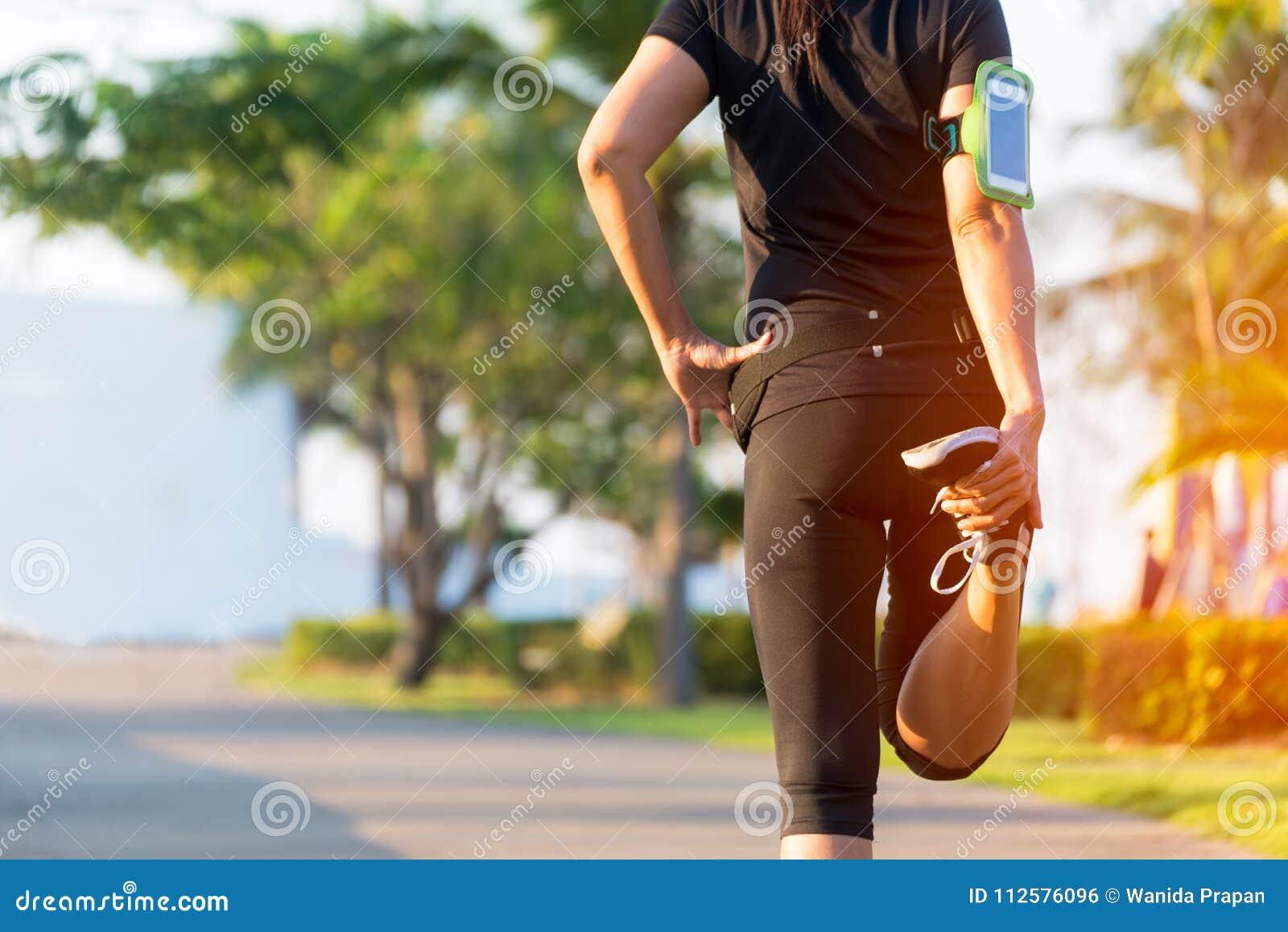 Vida saudável Corredor asiático da mulher da aptidão que estica os pés antes do exercício exterior da corrida no parque
