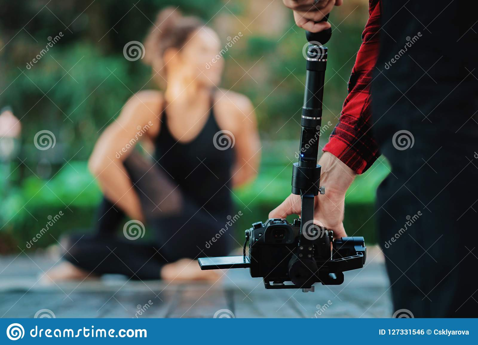 Video camera man operator working with professional equipment,filming recording. Cameraman shooting video of yoga