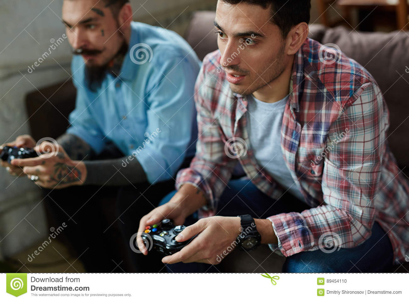 Portrait of two modern adult men, one of them heavily tattooed, holding  controllers and playing video game on couch, looking tense in competition