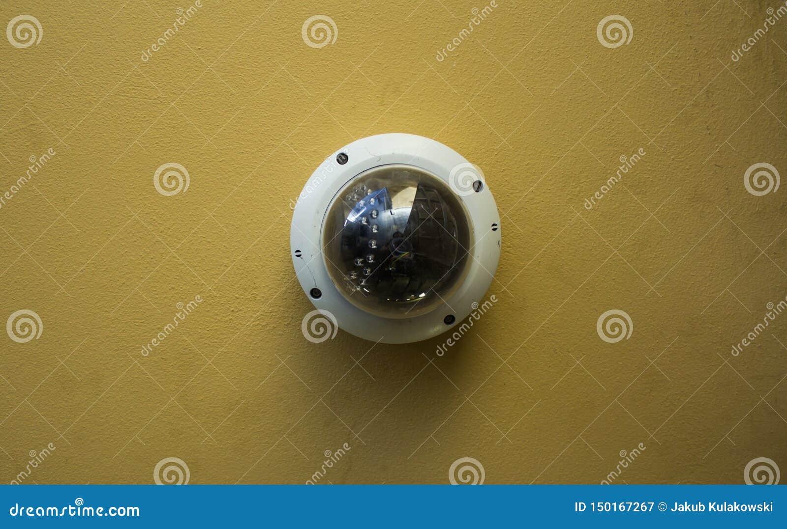 Videocamera di sicurezza rotonda moderna su un soffitto giallo
