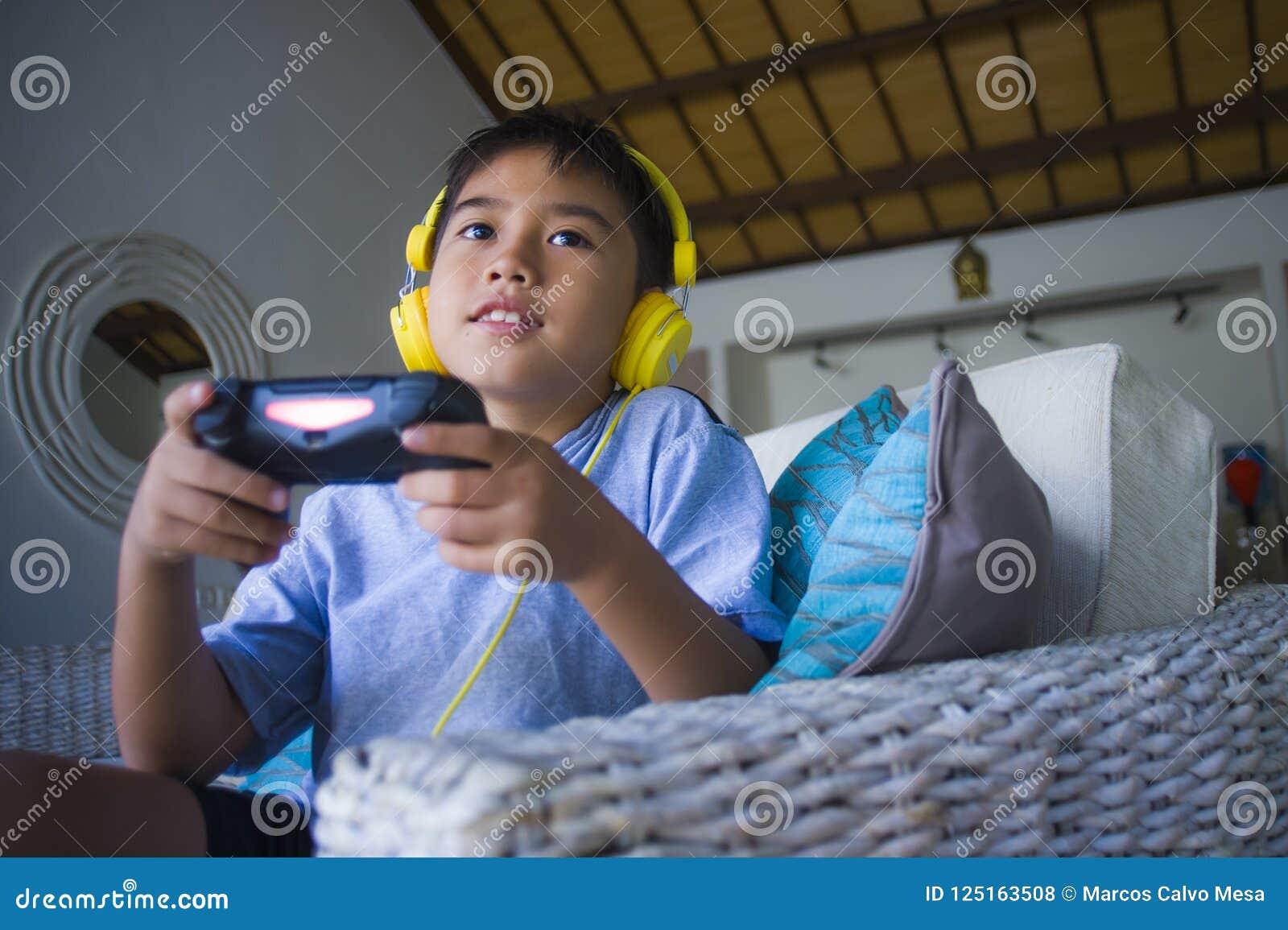 Videojuego que juega del niño latino en línea emocionado y feliz con los auriculares que detienen al regulador que goza divirtién