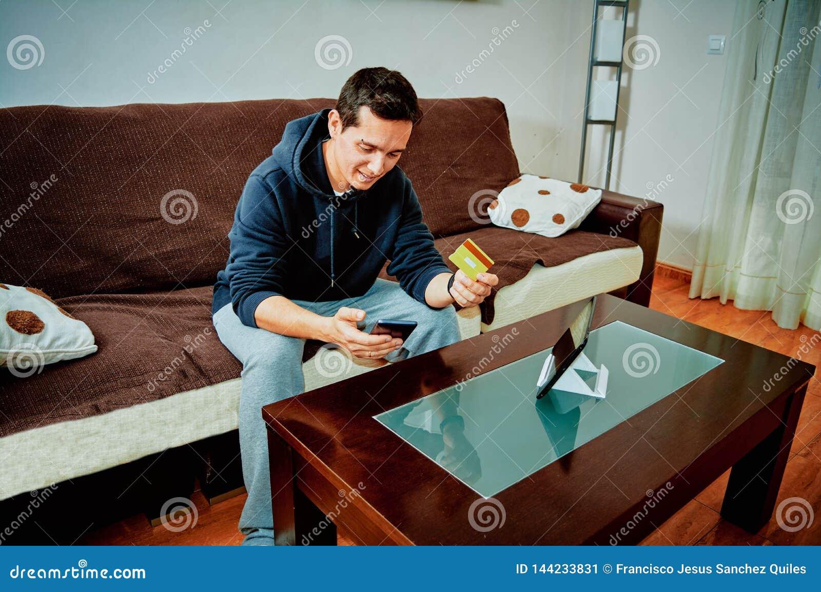 Videojuegos jovenes de la compra del muchacho sobre Internet con su tel?fono m?vil