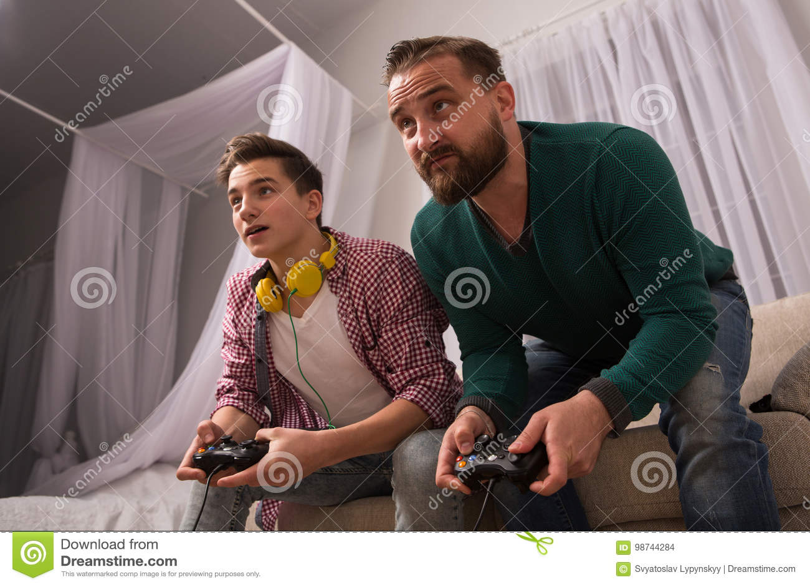 Videospelletjeconcept, vader en zoon die samen spelend console genieten van