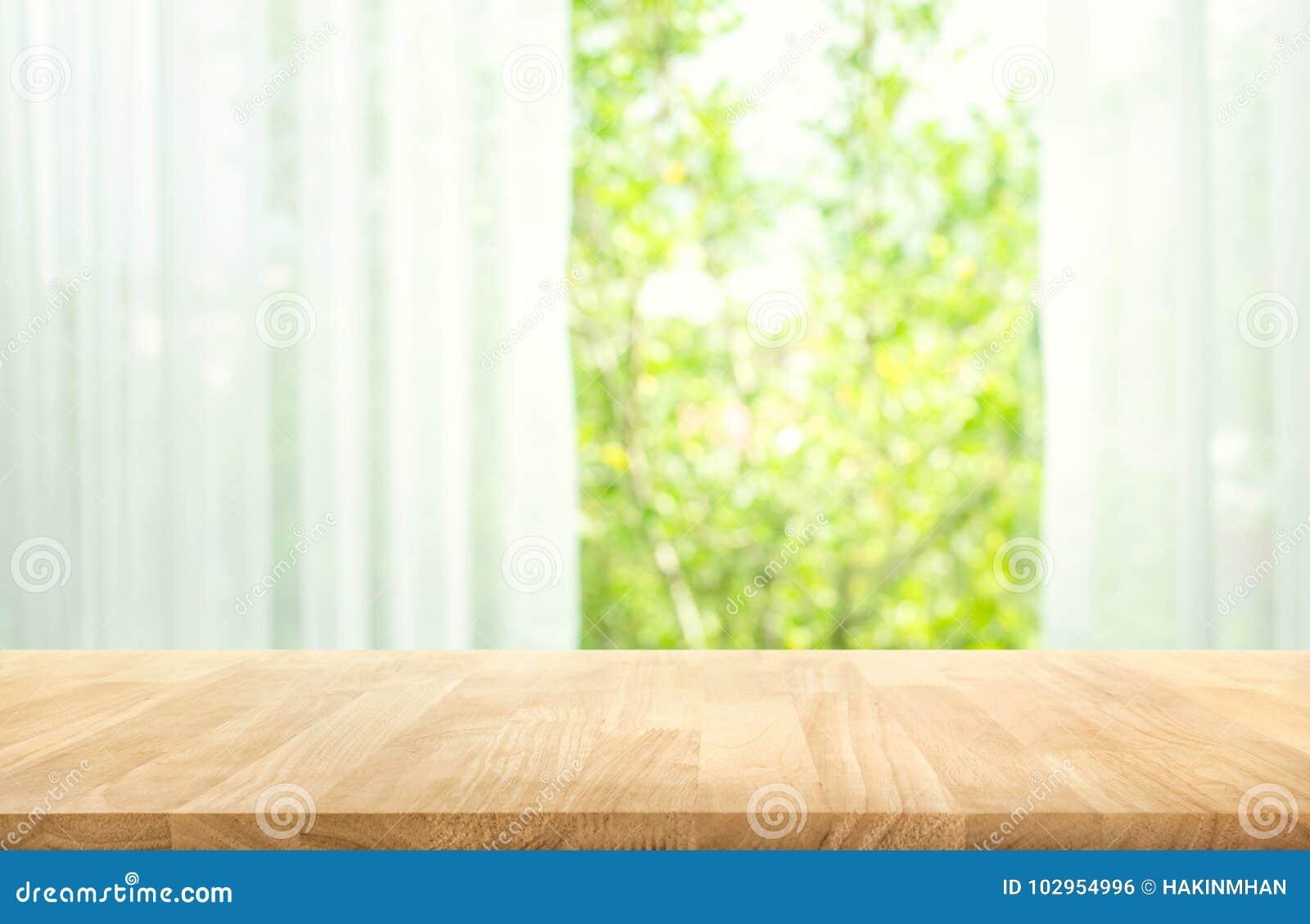 Videz du dessus de table en bois sur la tache floue du rideau avec le vert de vue de fenêtre du fond de jardin d arbre