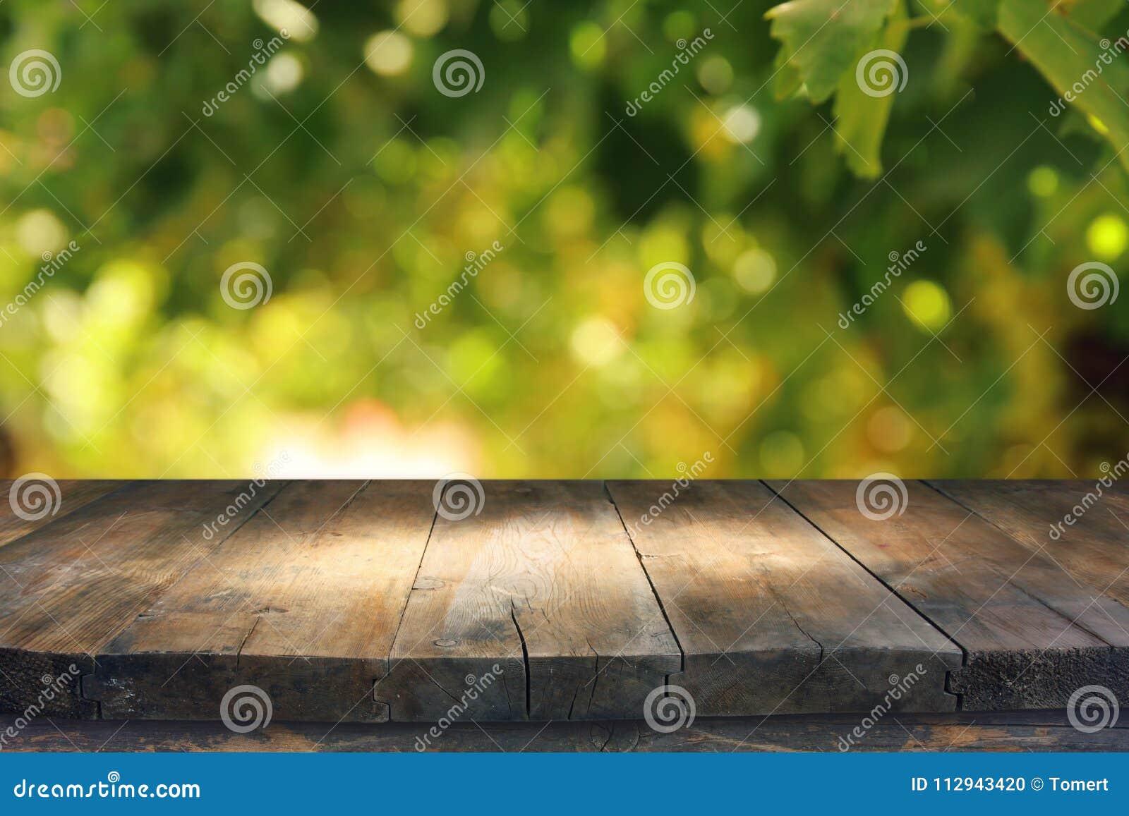 Videz la table rustique devant le fond vert de bokeh d abrégé sur ressort affichage de produit et concept de pique-nique