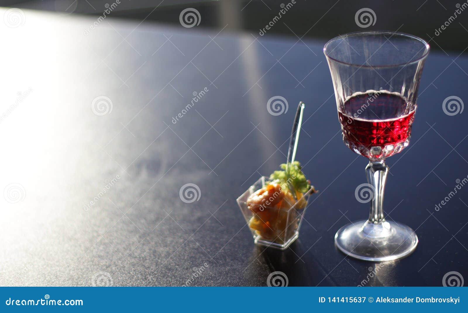 Vidrio con el vino en el top negro en oficina