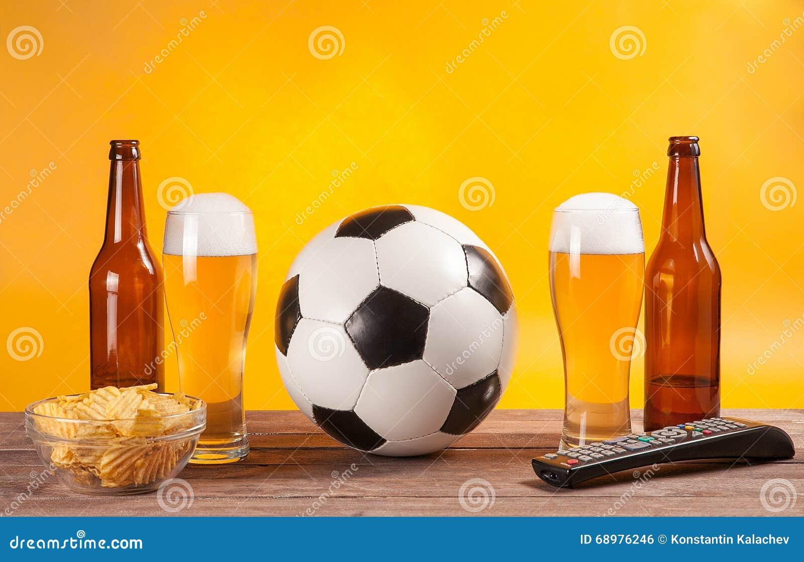 Vidrio con la cerveza y balón de fútbol cerca del telecontrol de la TV