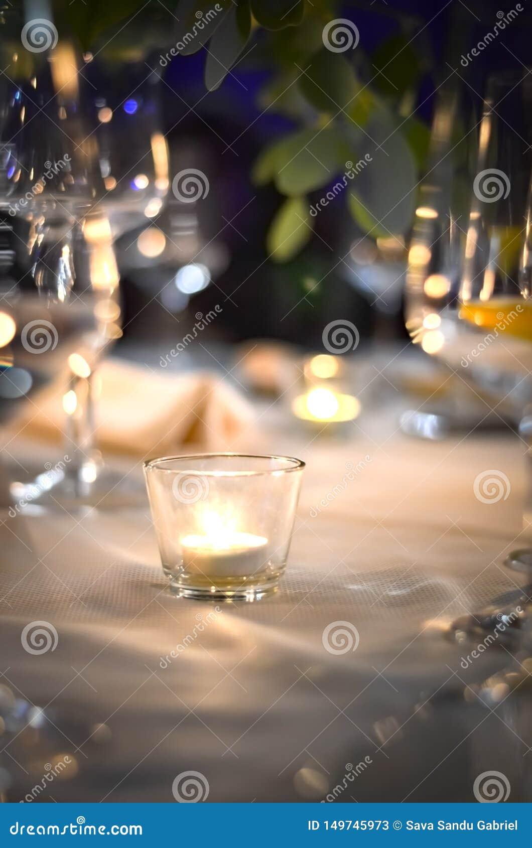 Vidrio con las velas encendidas dentro, en una tabla
