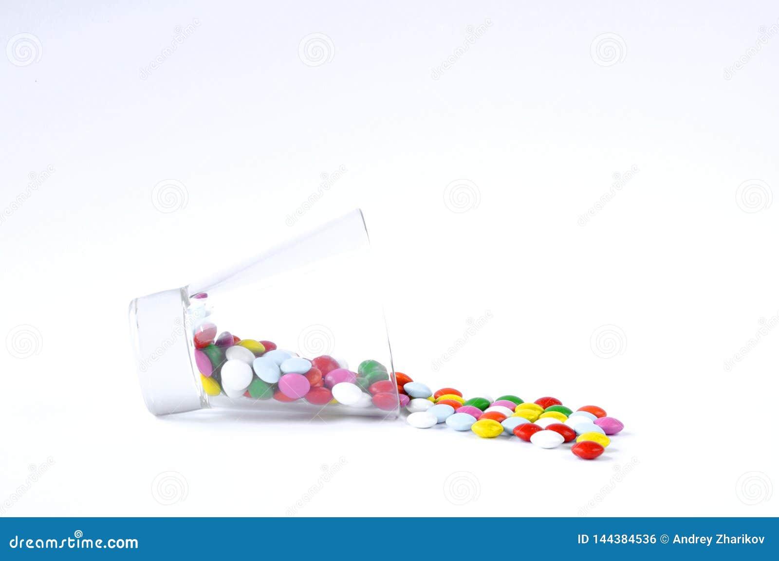 Vidrio con los dulces en un fondo blanco