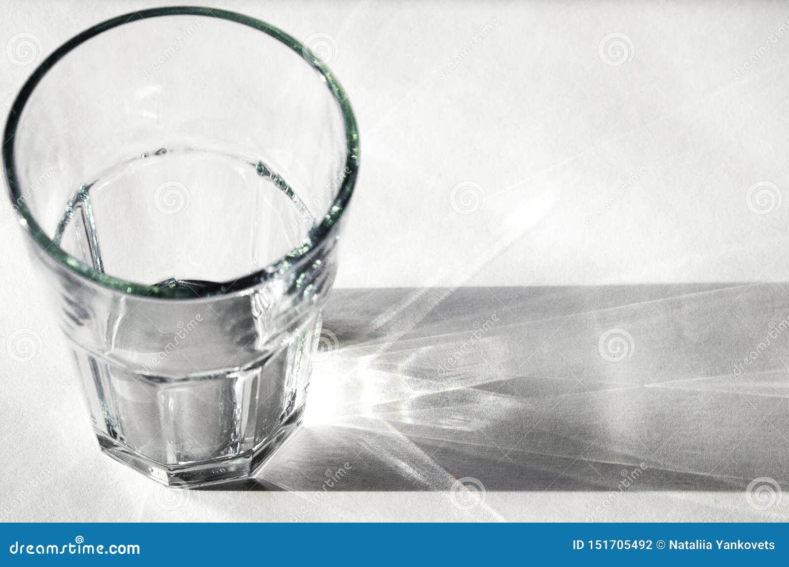 Vidrio de agua con las sombras fuertes en el fondo blanco