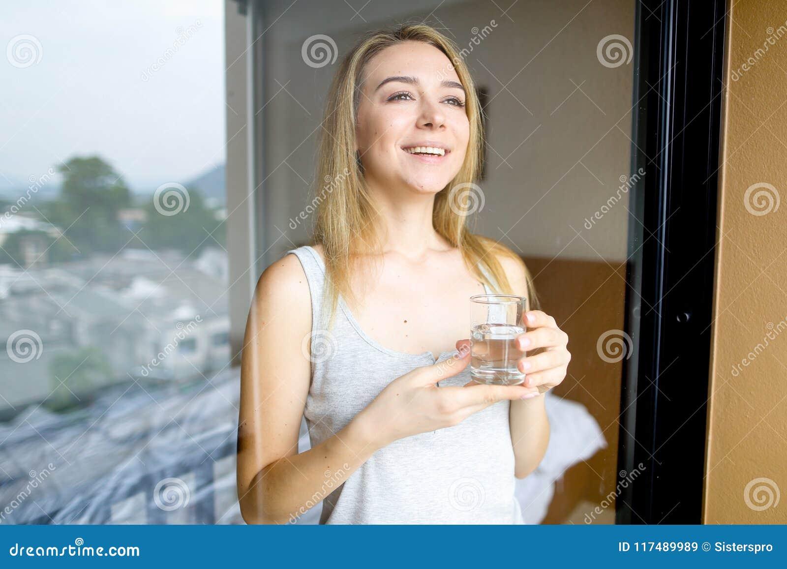 Vidrio de consumición caucásico joven de la persona femenina de agua por mañana en el hotel