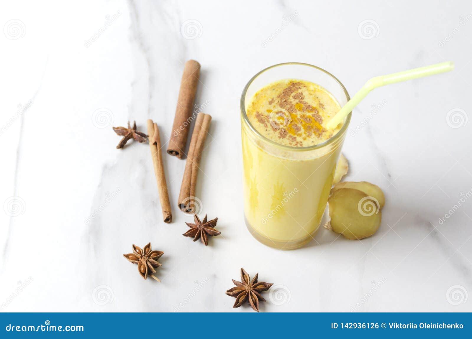 Vidrio de latte hecho en casa de la cúrcuma con canela, anís de estrella y pedazos de jengibre, paja de beber