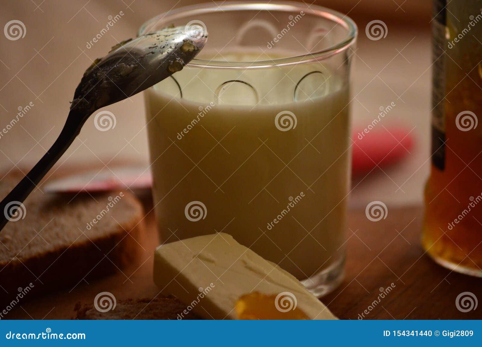 Vidrio de leche fresca, de cuchara con el atasco del albaricoque y de mantequilla