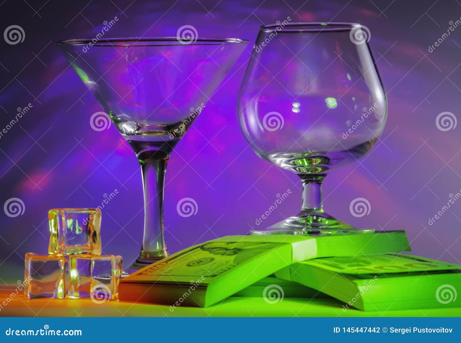 Vidrio de Martini así como el vidrio del coñac en paquetes del 100s de dólar y cubos de hielo con las luces violetas brillante