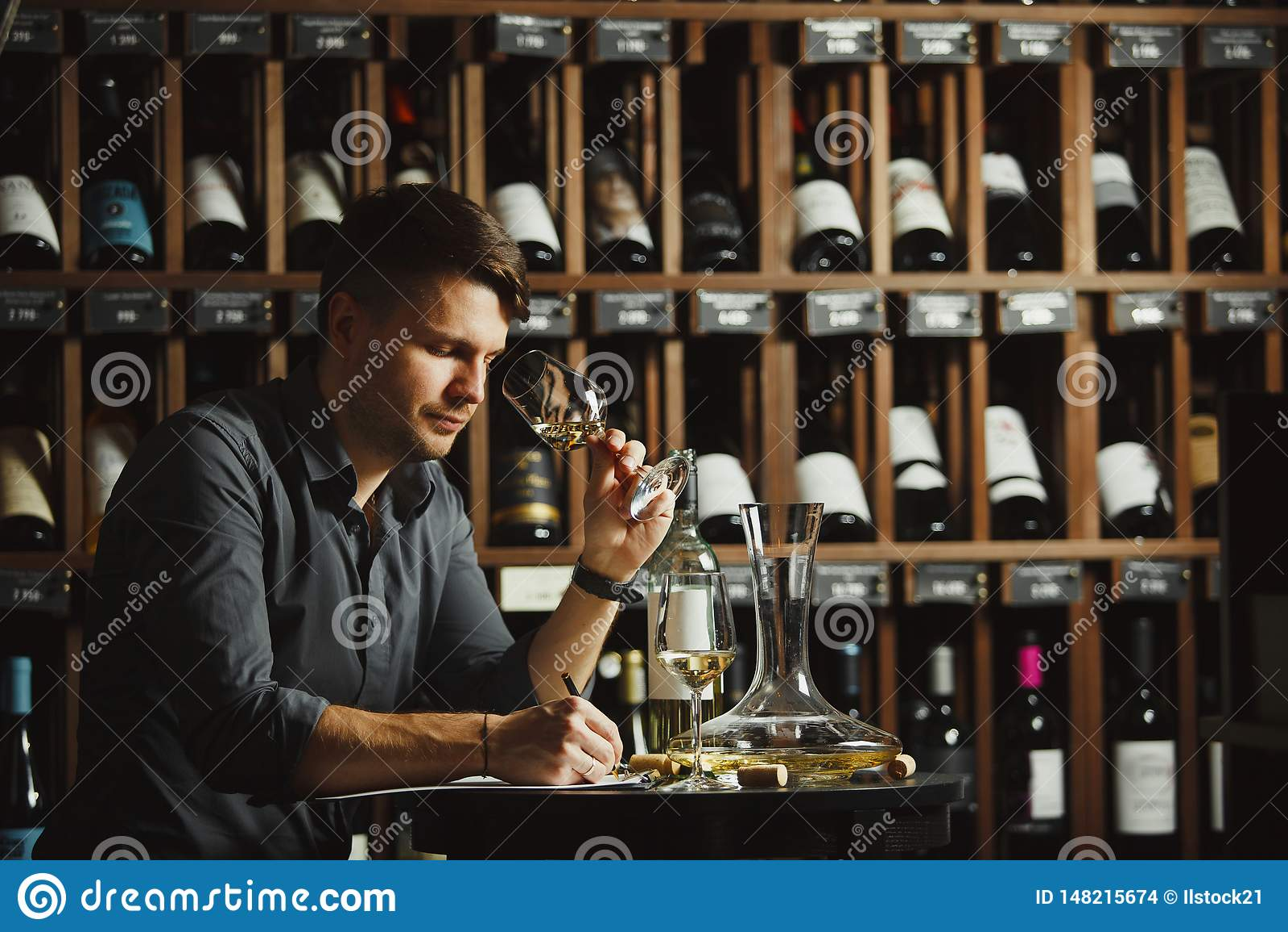 Vidrio degustating del vino blanco del Sommelier vertido
