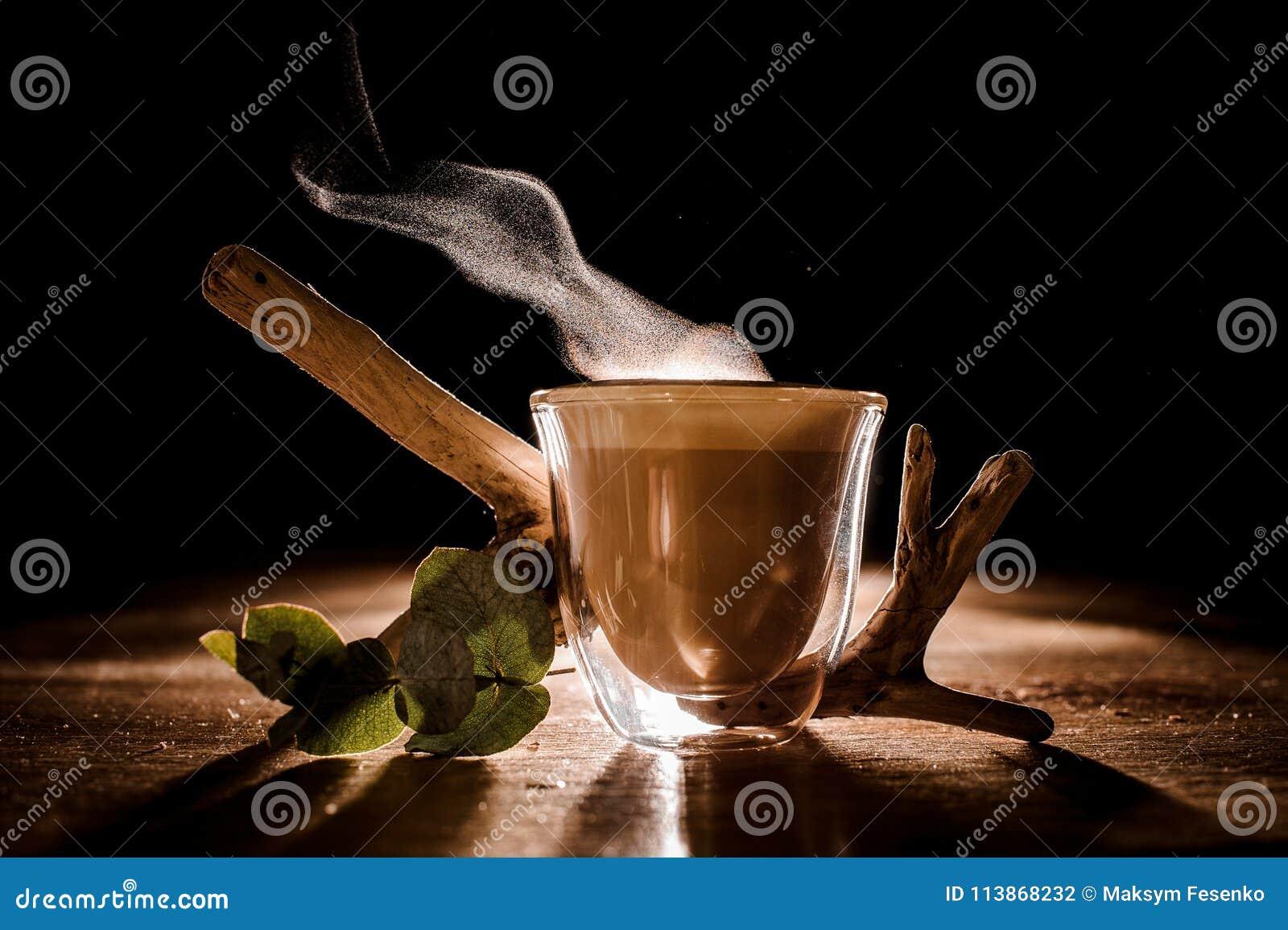 Vidrio transparente de un café caliente delicioso en el fondo oscuro