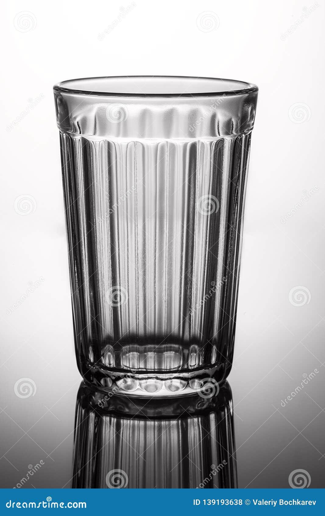 Vidrio vacío en fondo gris con puntos culminantes
