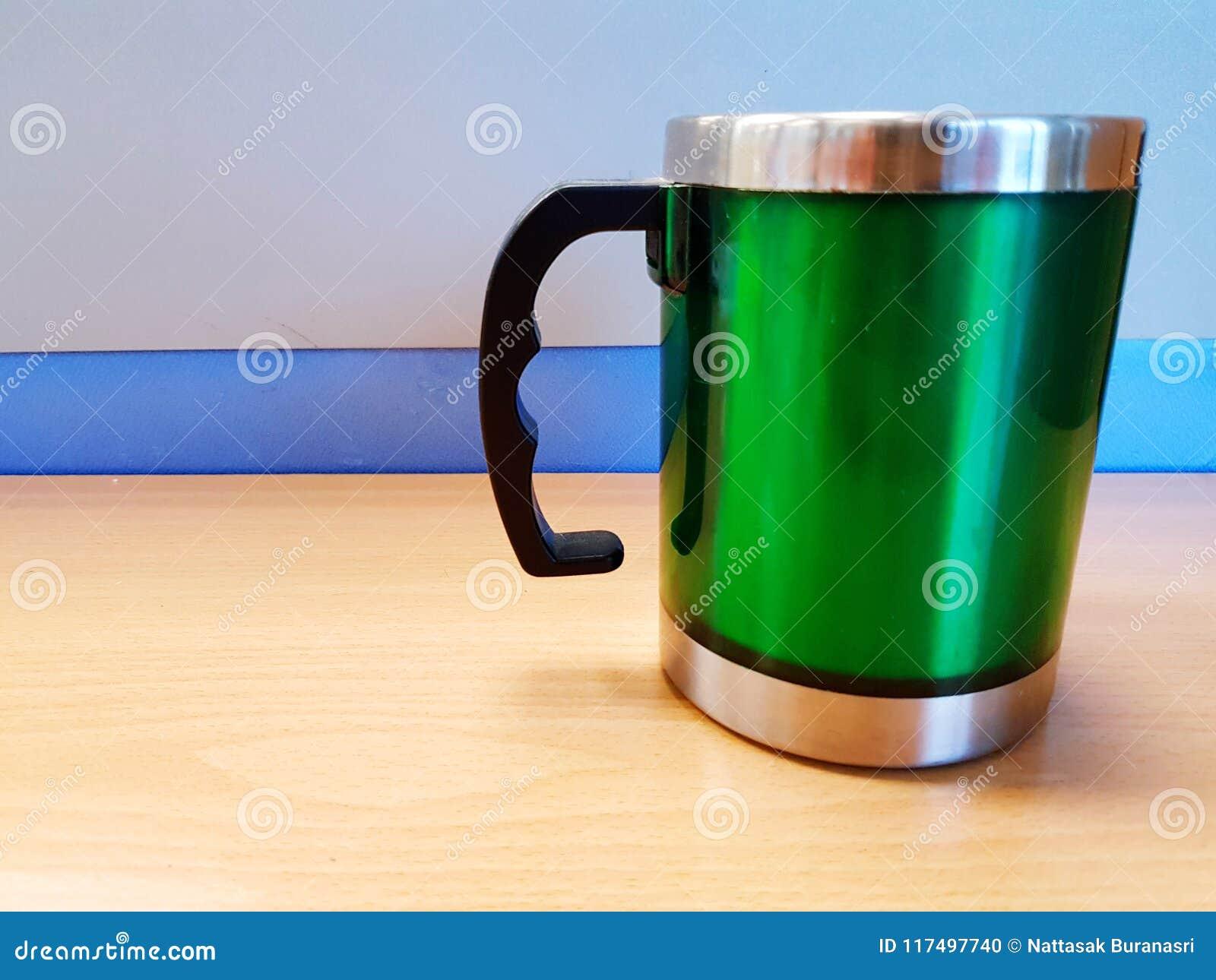 Vidrio verde verde del acero inoxidable con la manija negra en la tabla de madera con el fondo de la pared y el espacio azules de