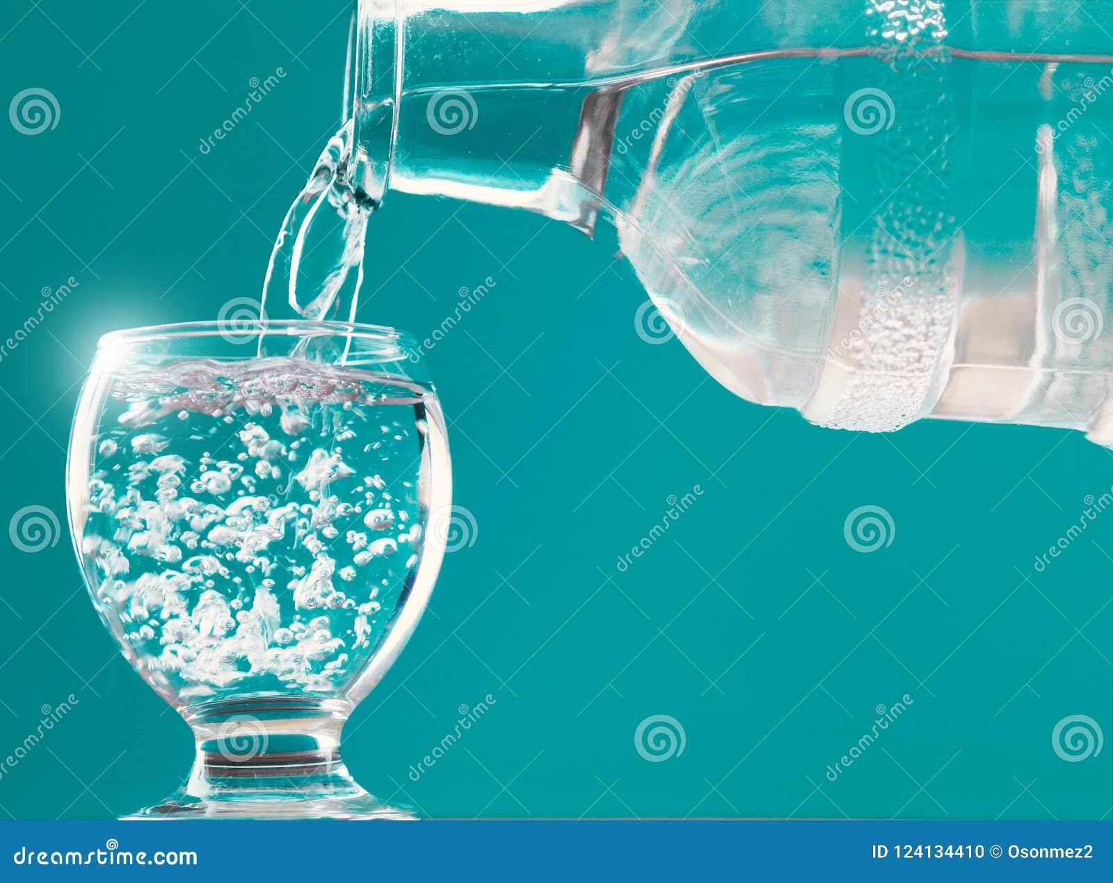 Vidrio y botella de agua de agua con el relleno del agua