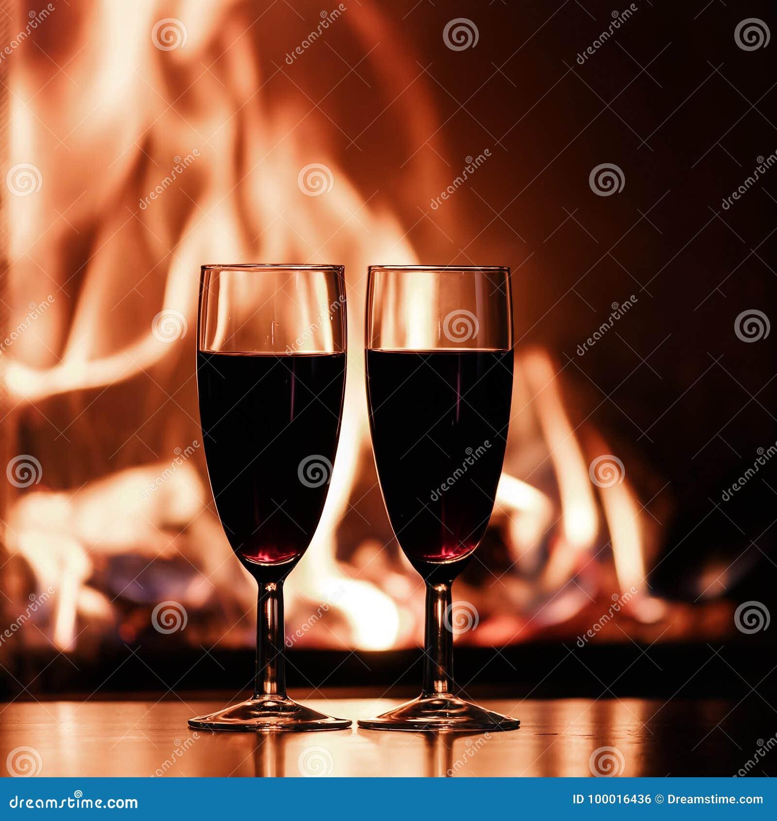 Vidrios de champán rojo por la chimenea