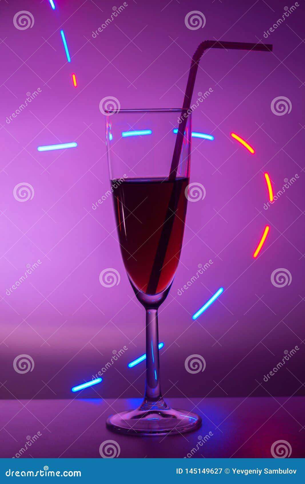 Vidrios de champ?n Vidrio o stemware con alcohol o un c?ctel en un fondo coloreado Un vidrio en la barra en un caf