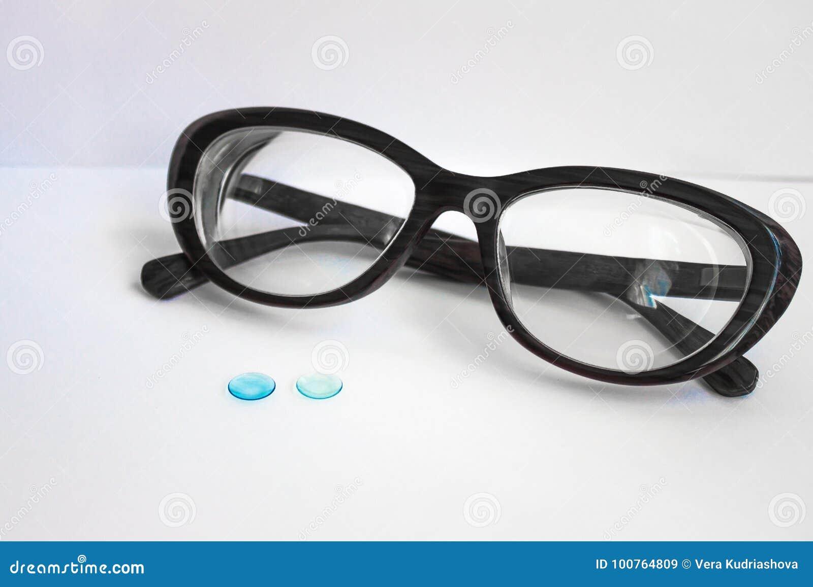 d4639e9385 Borde negro femenino para los vidrios, al lado de dos lentes de contacto  Fondo blanco, luz del día Una lente es más brillante La óptica para los  ojos, ...