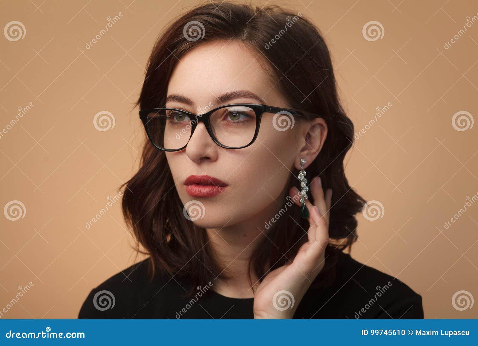 8b36951946a08 Retrato de las lentes que llevan y de la mirada de la chica joven lejos en  fondo del estudio