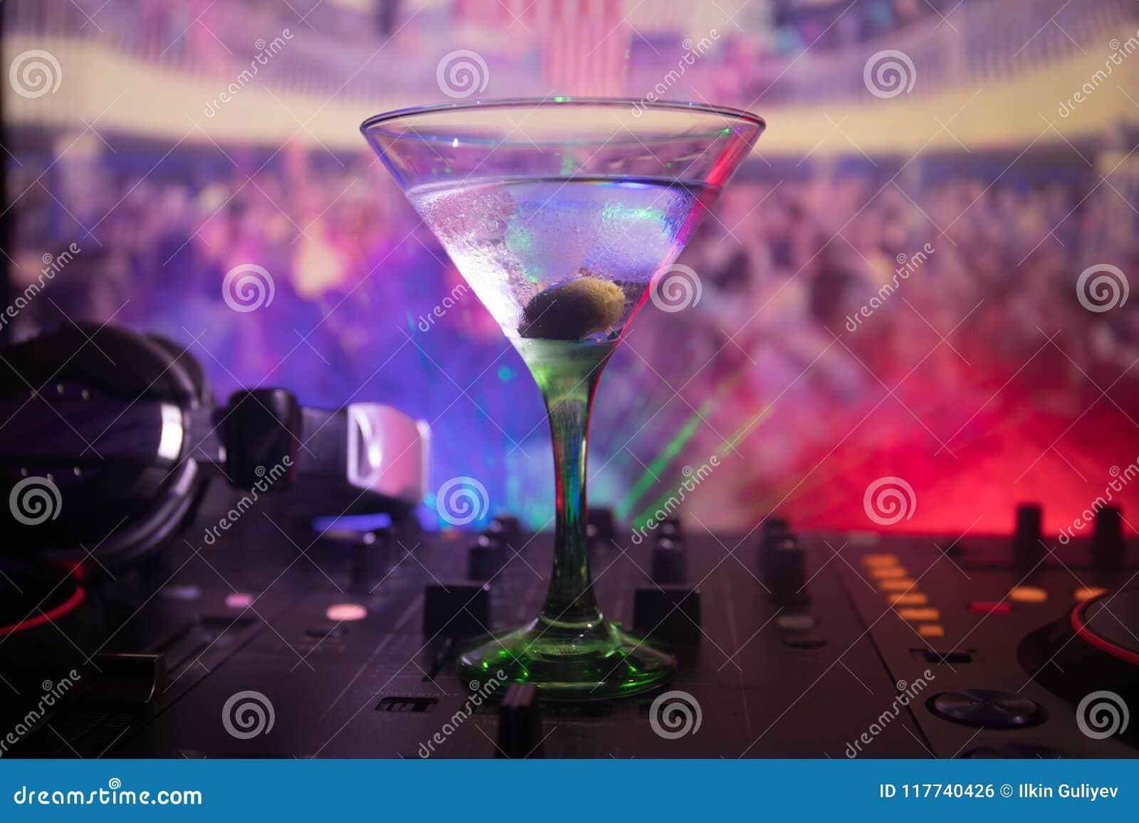 Vidro com o martini com azeitona para dentro no controlador do DJ no clube noturno Console do DJ com bebida do clube no partido d
