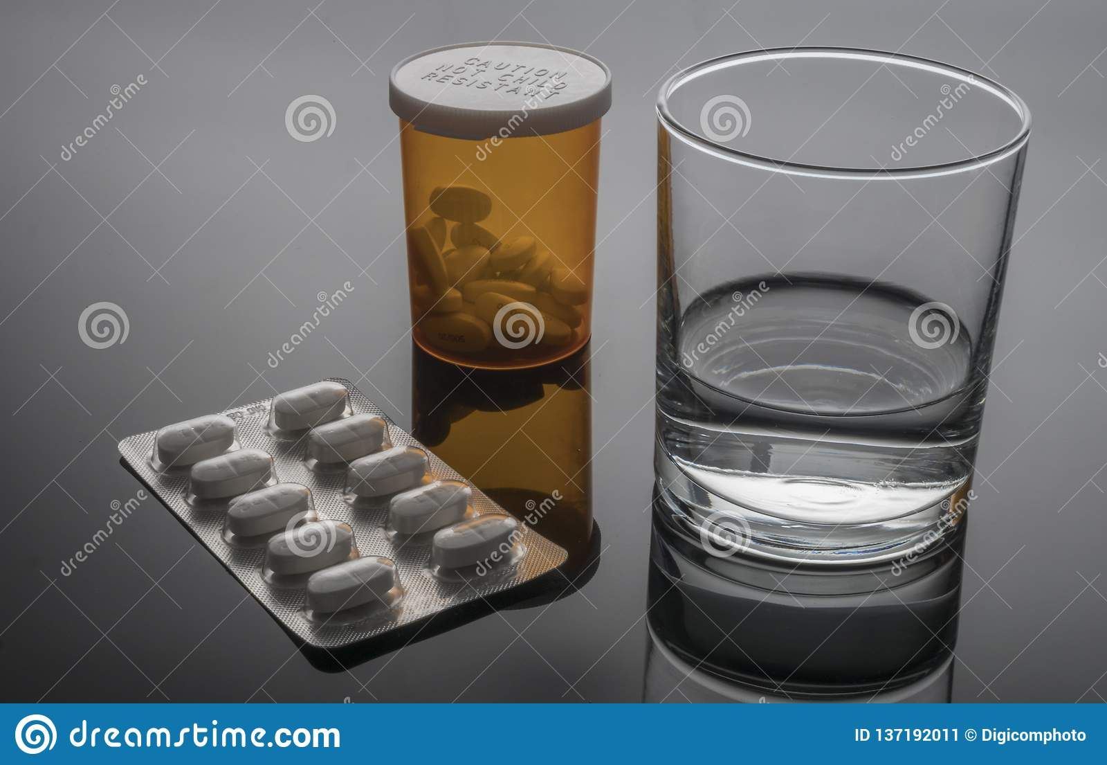 Vidro da água ao lado do bloco de bolha dos comprimidos