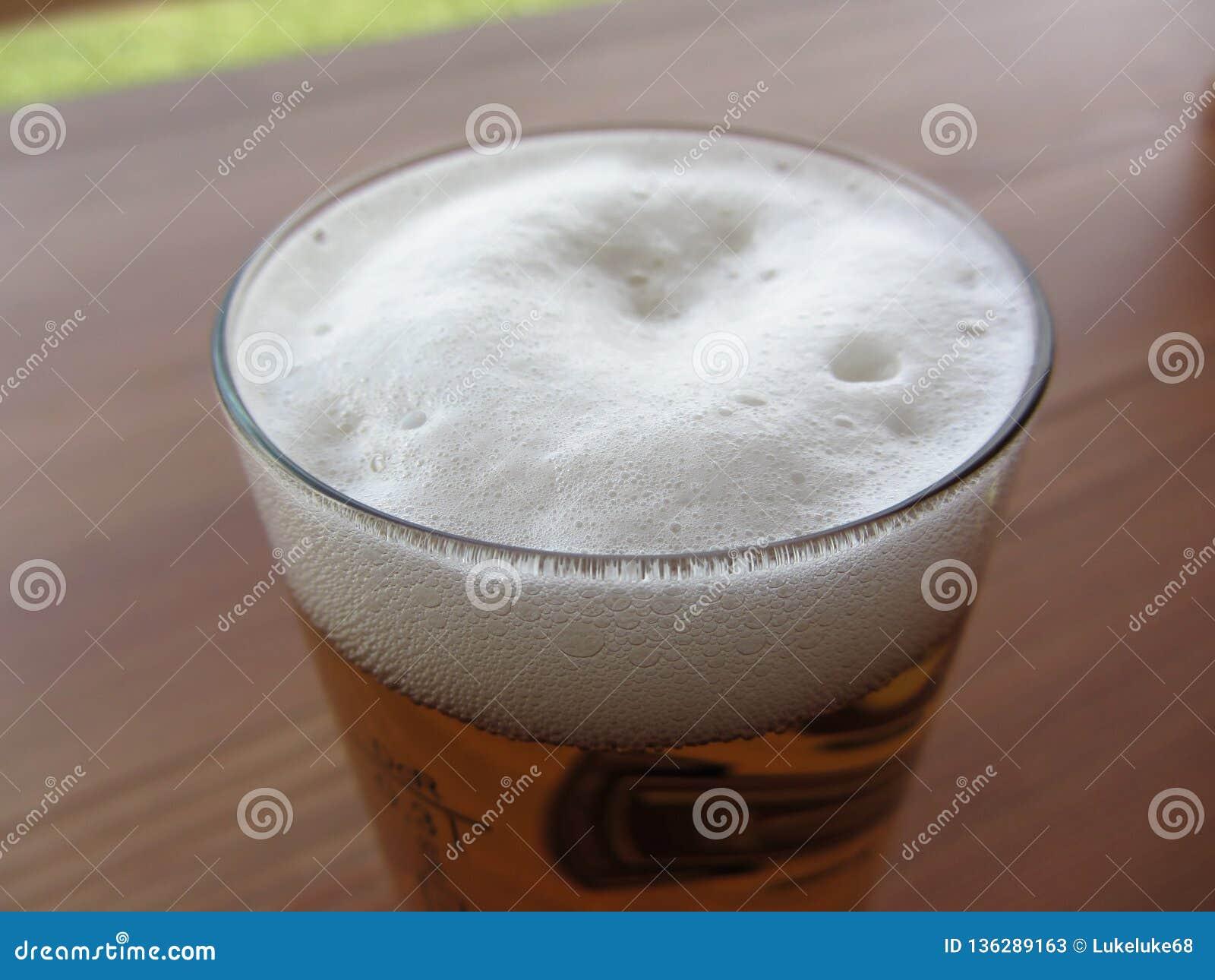 Vidro da cerveja na tabela Close up da espuma da cerveja