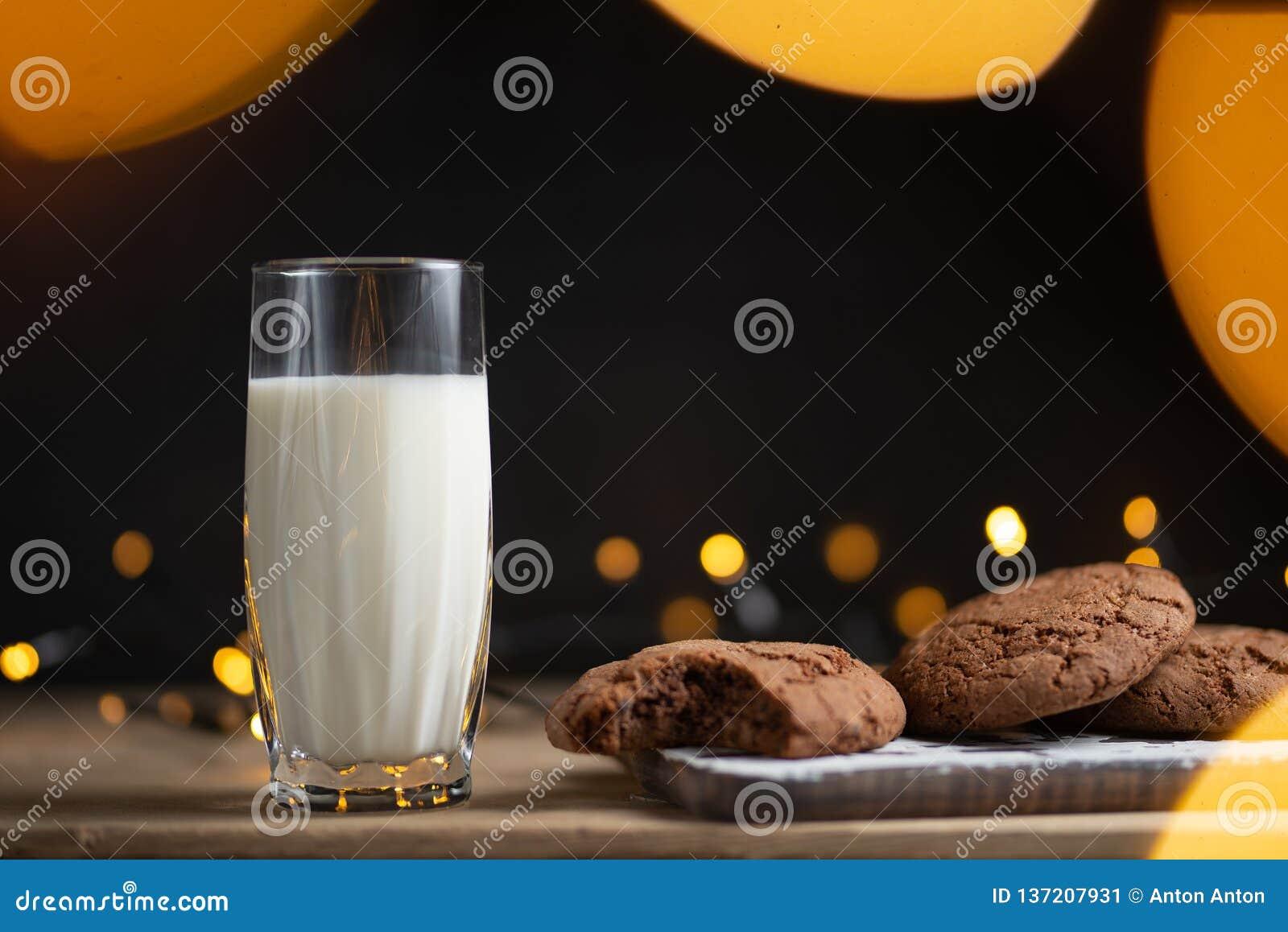 Vidro da foto do leite com cookies caseiros, fundo bonito com luzes no borrão