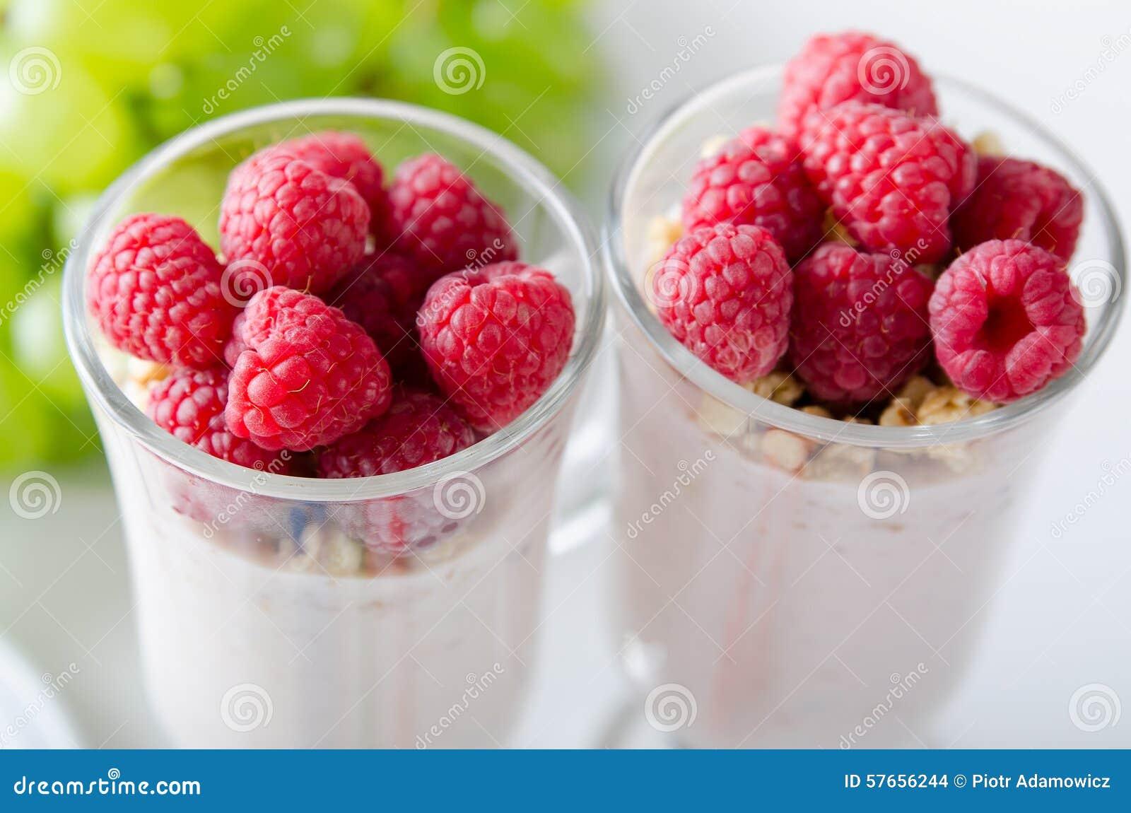 Vidro da sobremesa com iogurte, as bagas frescas e o muesli